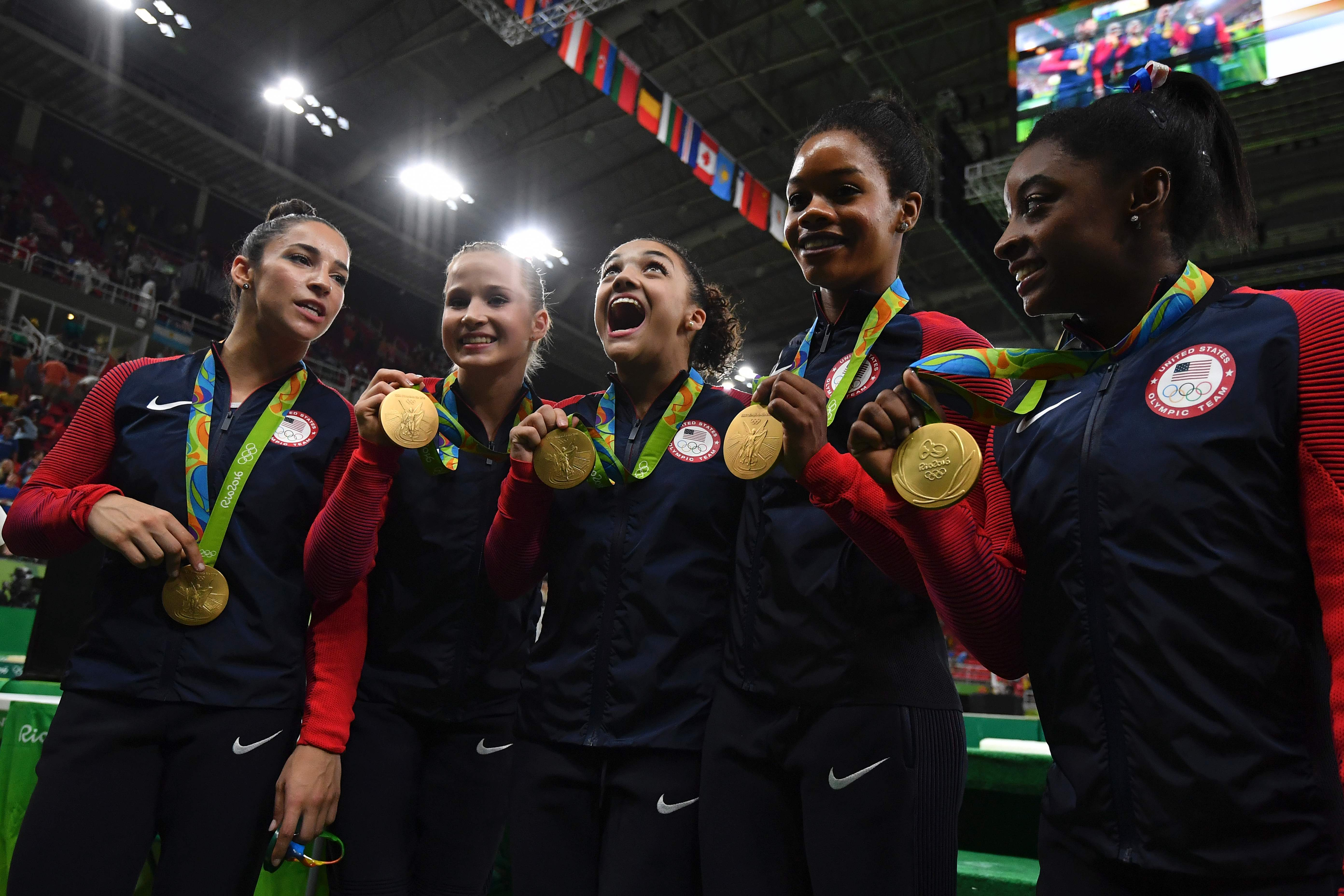 US gymnasts Alexandra Raisman, Madison Kocian, Lauren Hernandez, Gabrielle Douglas and Simone Biles celebrate with their medals on the podium during the women's team final Artistic Gymnastics at the Olympic Arena during the Rio 2016 Olympic Games in Rio de Janeiro on August 9, 2016.