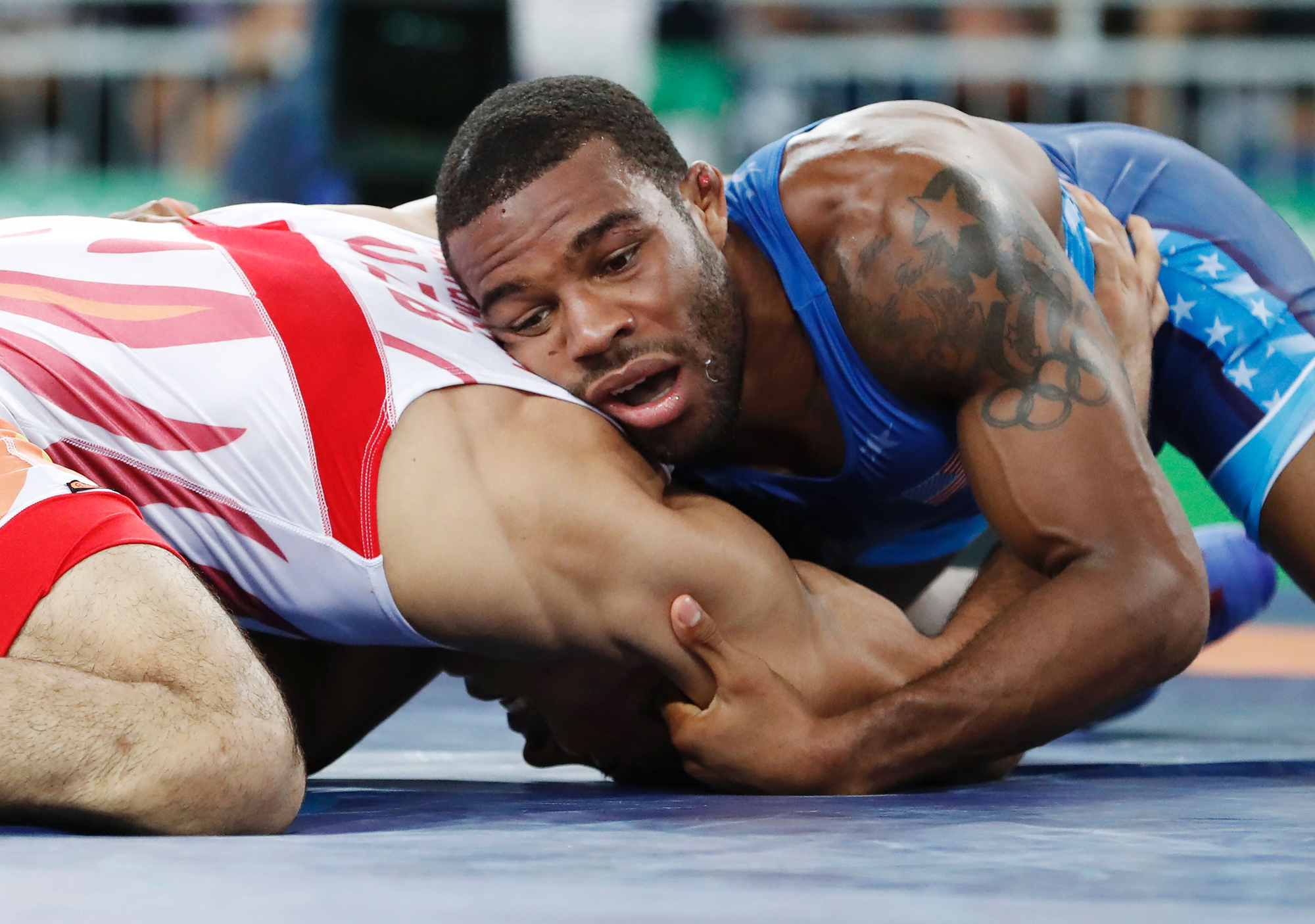 Uzbekistan's Bekzod Abdurakhmonov (red) wrestles with USA's Jordan Ernest Burroughs in their men's 74kg freestyle repechage round 2 match on August 19, 2016, during the wrestling event of the Rio 2016 Olympic Games at the Carioca Arena 2 in Rio de Janeiro.