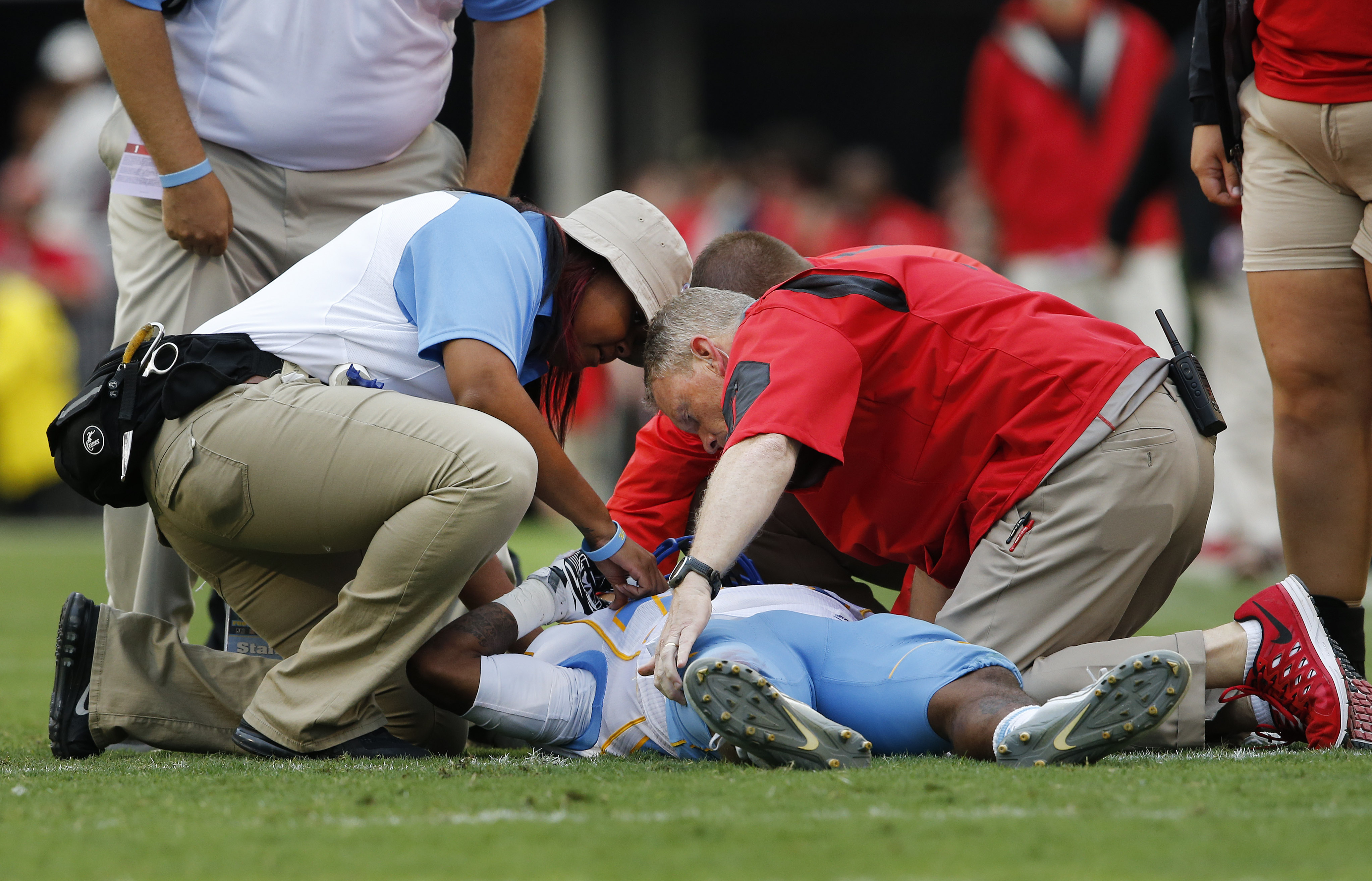 Members of the Southern and Georgia training staff tend to Southern wide receiver Devon Gales (33) after he was injured in the second half of an NCAA college football game against Georgia Saturday, Sept. 26, 2015, in Athens , Ga. Gales was placed on backboard and taken off the field on a cart.