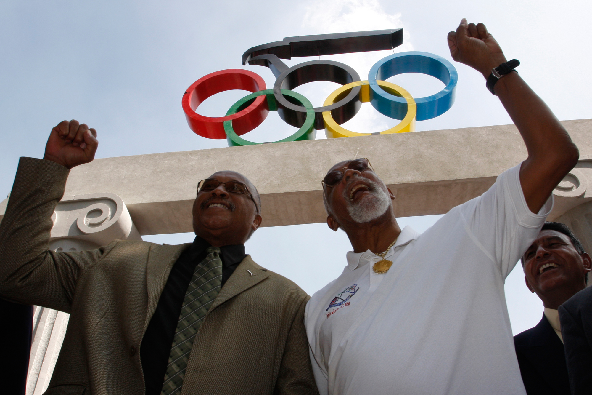 U.S. Olympic medallists Tommie Smith, left, and John Carlos hold up their fists at the Mexican Olympic Committee building in Mexico City, Wednesday, Oct. 15, 2008.