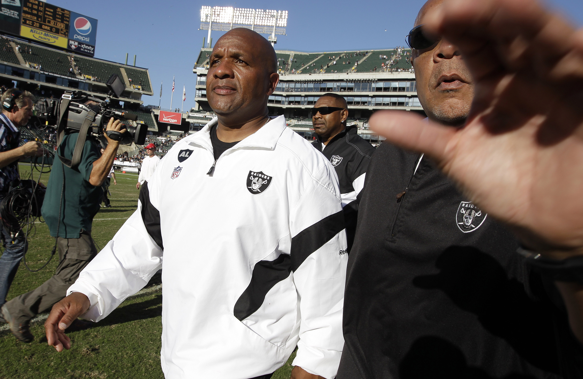 Oakland Raiders head coach Hue Jackson, left, walks off the field after an NFL football game against the Kansas City Chiefs in Oakland, Calif., Sunday, Oct. 23, 2011.