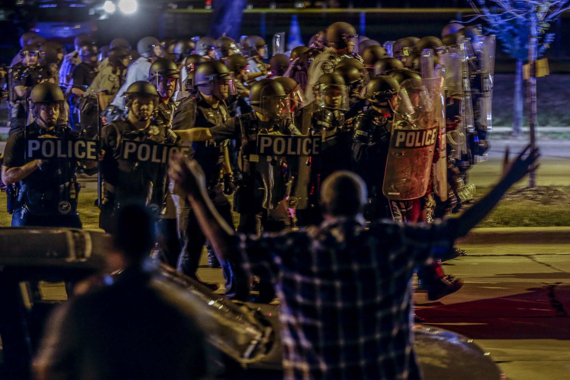Police move in on a group of protesters throwing rocks at them in Milwaukee, Sunday, Aug. 14, 2016. Police said one person was shot at a Milwaukee protest on Sunday evening and officers used an armored vehicle to retrieve the injured victim during a second night of unrest over the police shooting of a black man, but there was no repeat of widespread destruction of property.