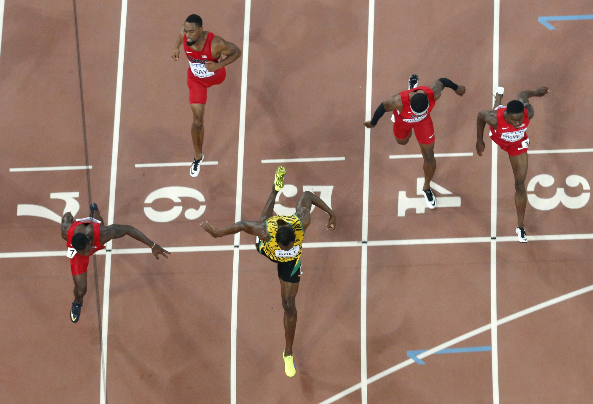 Jamaica's Usain Bolt, center, crosses the finish line to win the gold medal in the men's 100m ahead of United States' Justin Gatlin at the World Athletics Championships at the Bird's Nest stadium in Beijing, Sunday, Aug. 23, 2015.