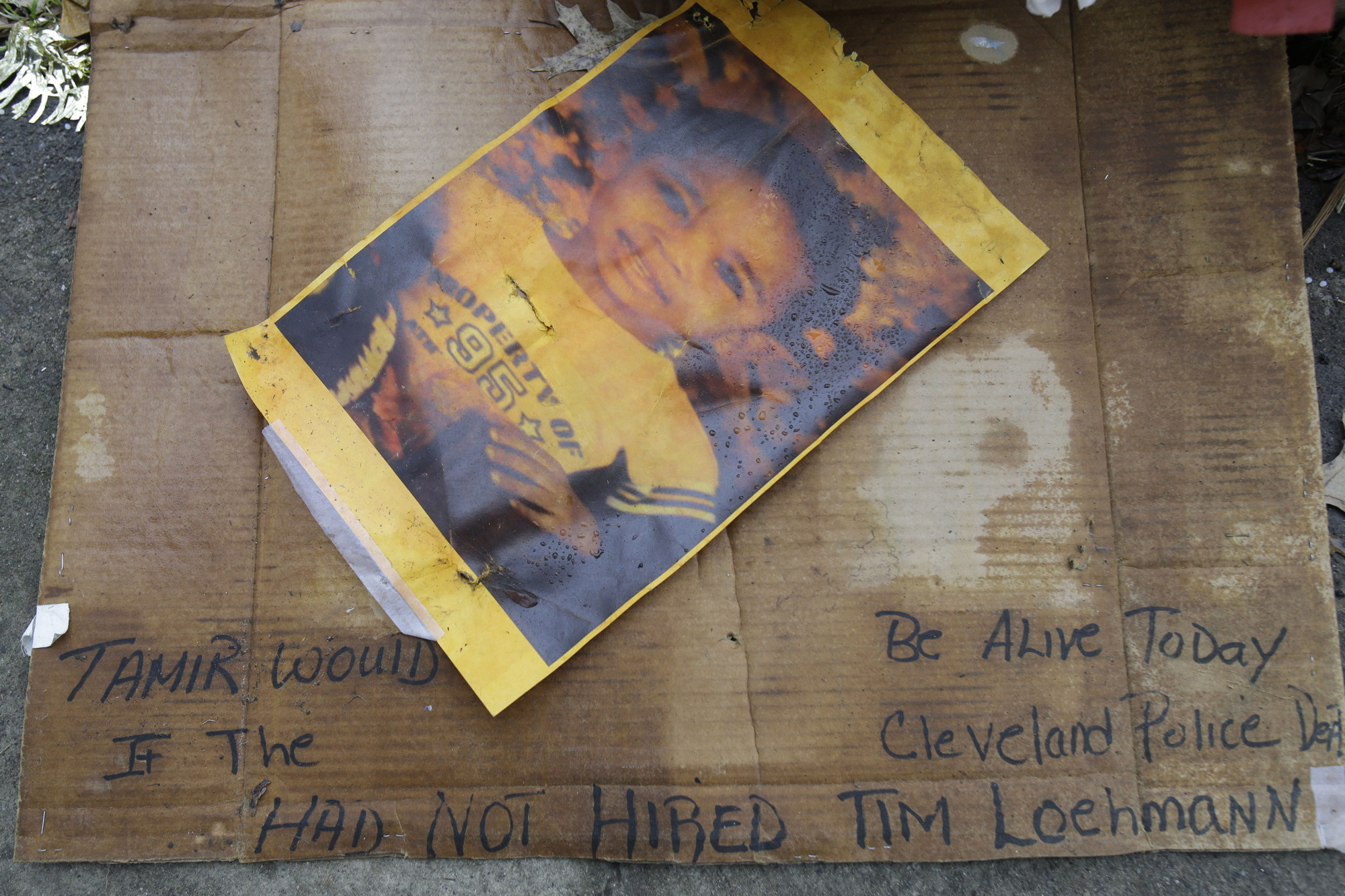 A photo of Tamir Rice rests on the ground near a memorial outside the Cudell Recreation Center, Tuesday, Dec. 29, 2015, in Cleveland. A grand jury on Monday declined to criminally indict the two officers in Tamir's killing in November 2014 at the recreation center.