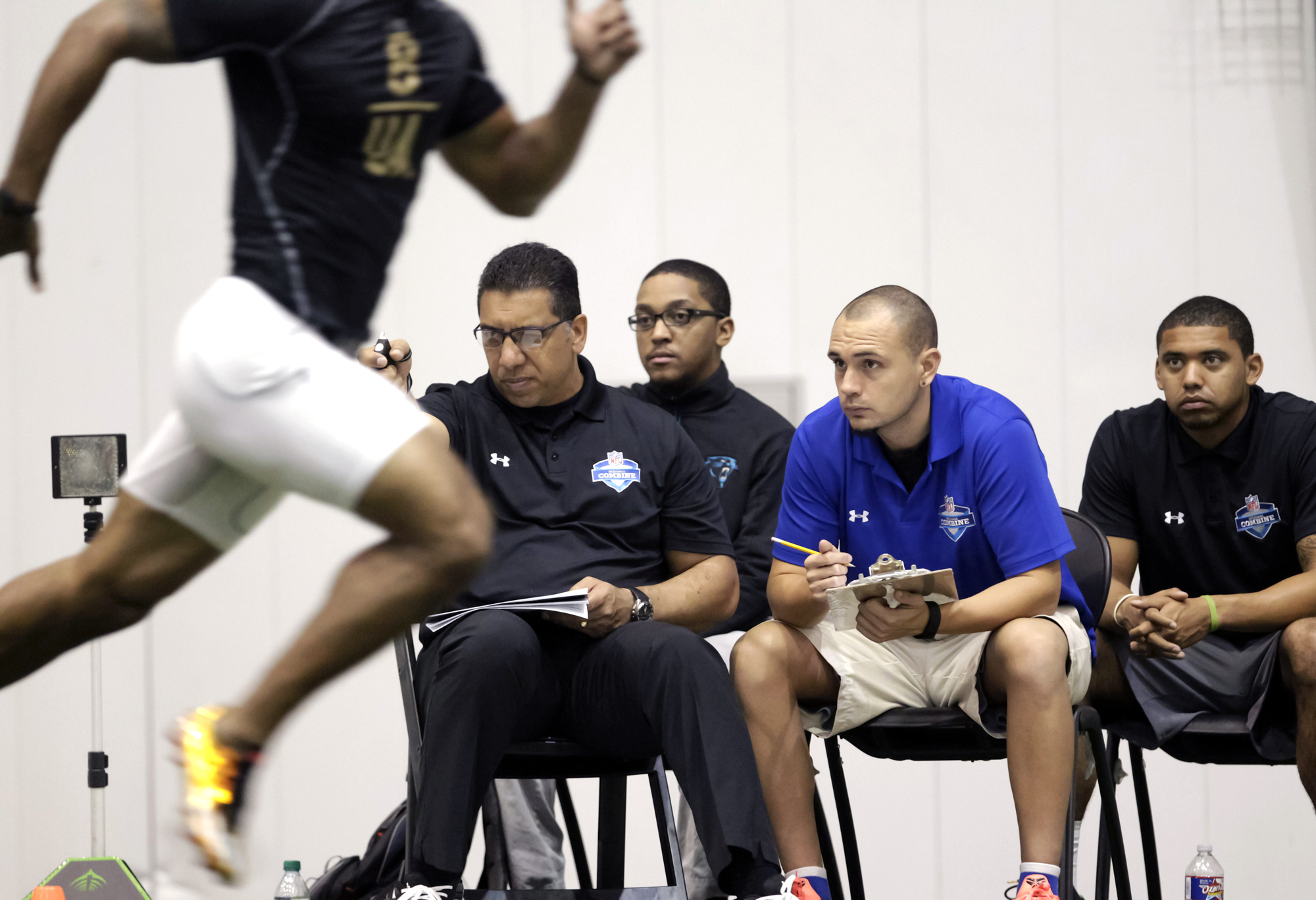 Junior Tagaloa, national director for the NFL Regional Combines, second from left, times McNeese State cornerback Gabriel Hamner in the 40-yard dash during the NFL football regional combine at the New Orleans Saints training facility in Metairie, La., Sunday, March 13, 2016.