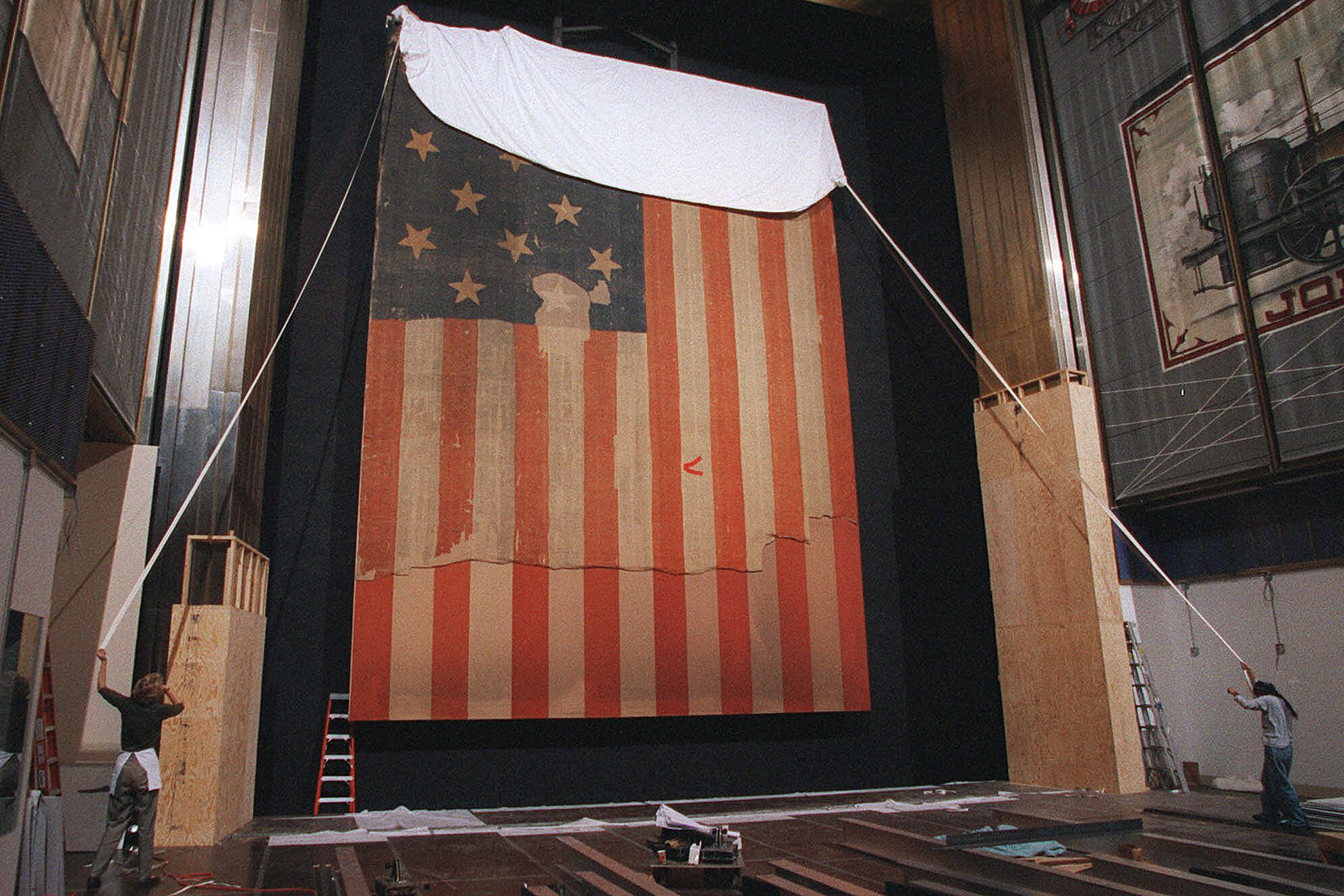 In this Nov. 20, 1998 file photo, Workers at the Smithsonian's National Museum of American History in Washington cover the flag that inspired the Star Spangled Banner, prior to the flag's restoration.