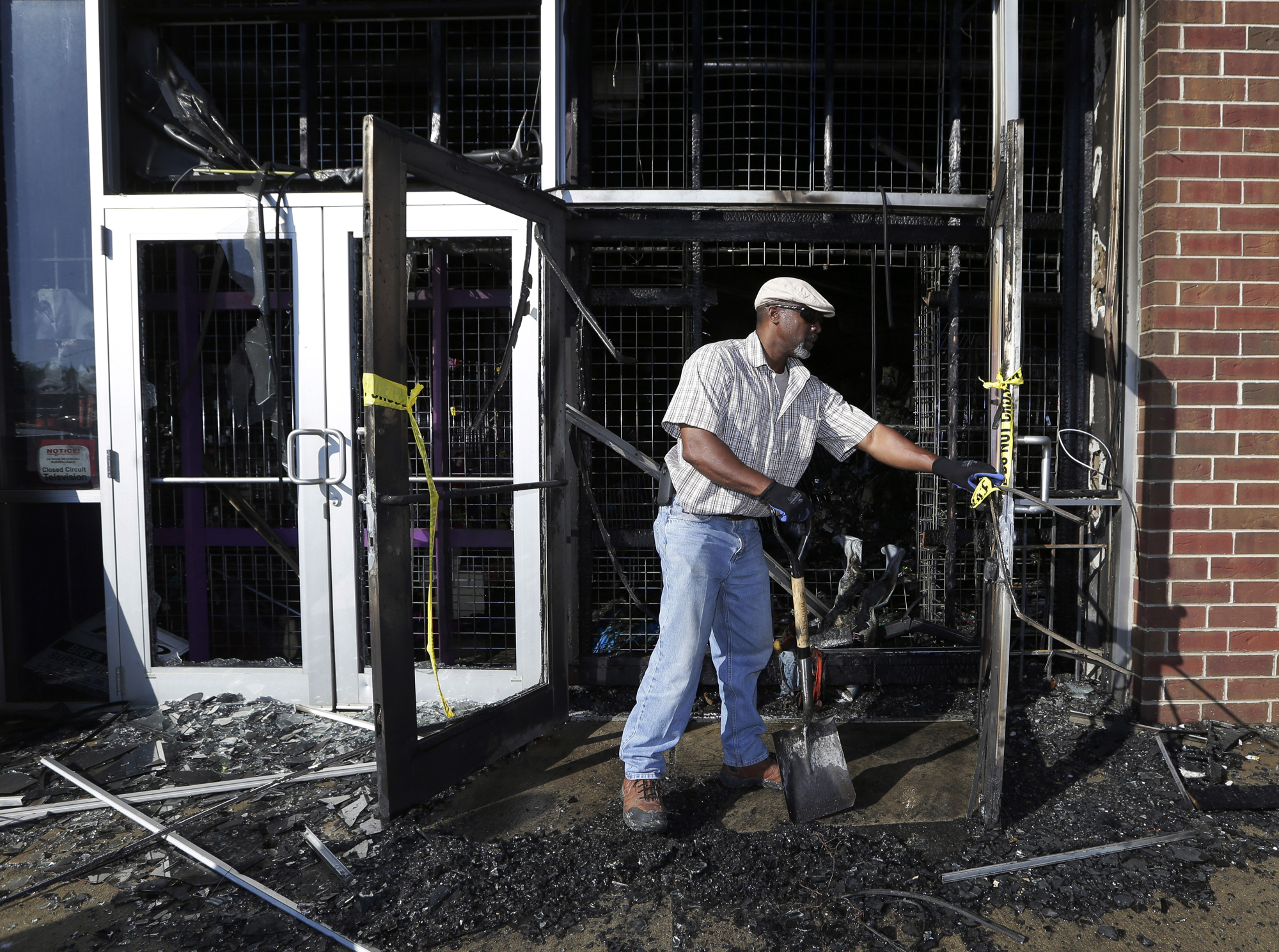 A city of Milwaukee employee cleans up a gutted Jet Beauty Supply, which was destroyed by fire and looting, in Milwaukee on Sunday, Aug. 14, 2016. The black man whose killing by police touched off rioting in Milwaukee was shot by a black officer after turning toward him with a gun in his hand, the police chief said Sunday, as Wisconsin's governor put the National Guard on standby against any further violence on the city's mostly black north side.