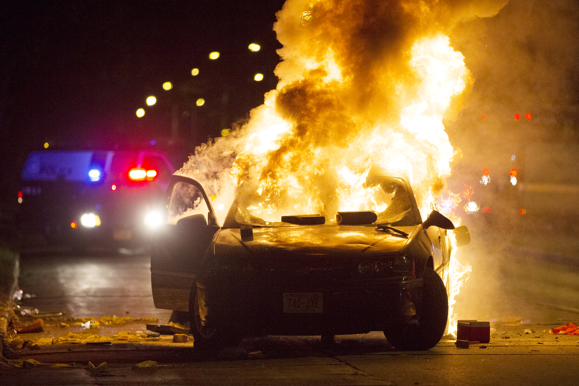 A car burns as a crowd of more than 100 people gathers following the fatal shooting of a man in Milwaukee, Saturday, Aug. 13, 2016. The Milwaukee Journal Sentinel reported that officers got in their cars to leave at one point, and some in the crowd started smashing a squad car's window, and another vehicle, pictured, was set on fire. The gathering occurred in the neighborhood where a Milwaukee officer shot and killed a man police say was armed hours earlier during a foot chase.