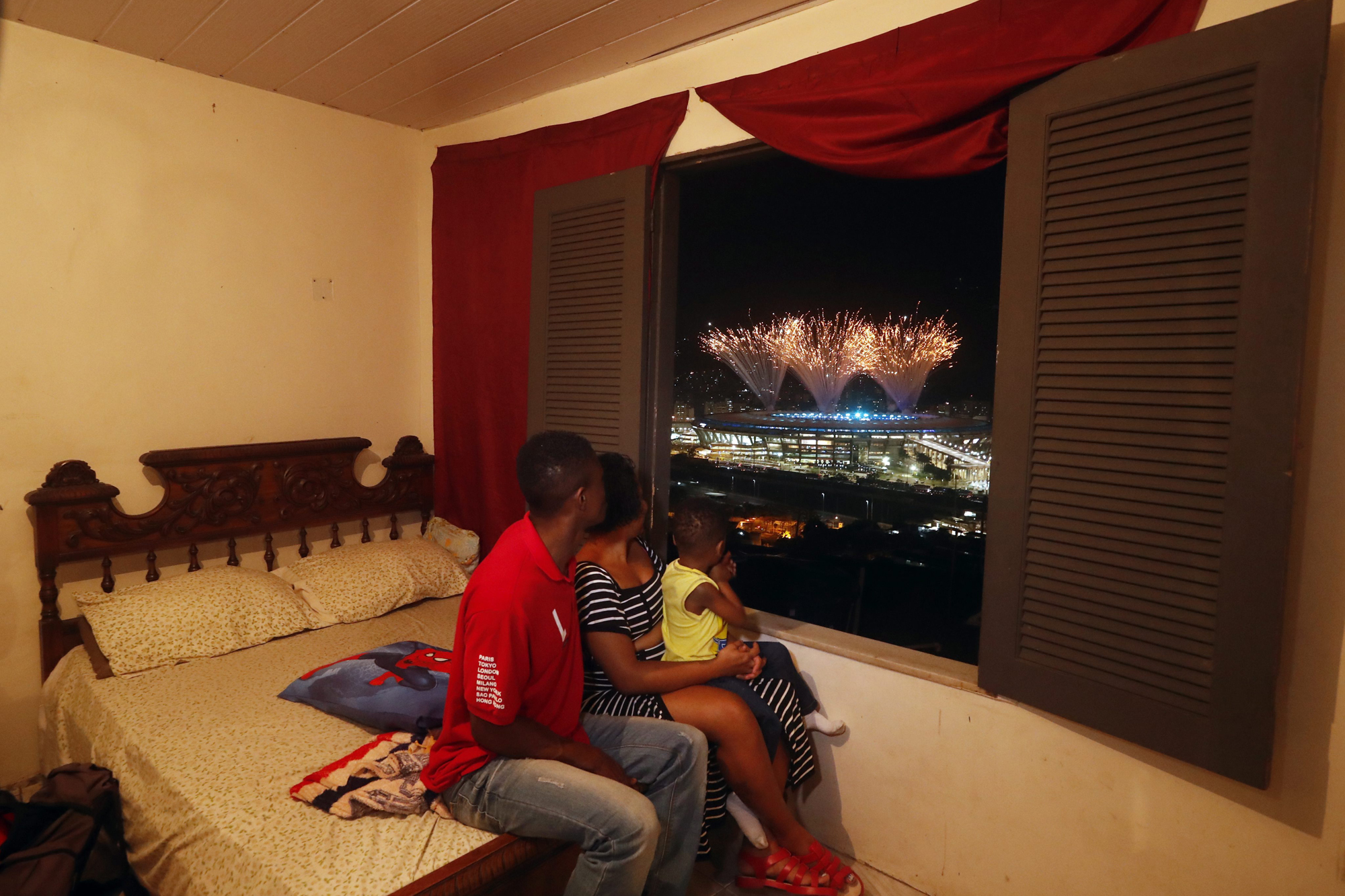 Hermes Felicio, Jaine Espirito Santo and their 3-year old son Hemerson da Costa in the Mangueira favela near the Maracana stadium watch fireworks going off at the start of the opening ceremony of the Rio 2016 Olympic Games at the famous stadium in Rio de Janeiro, Brazil, 05 August 2016.