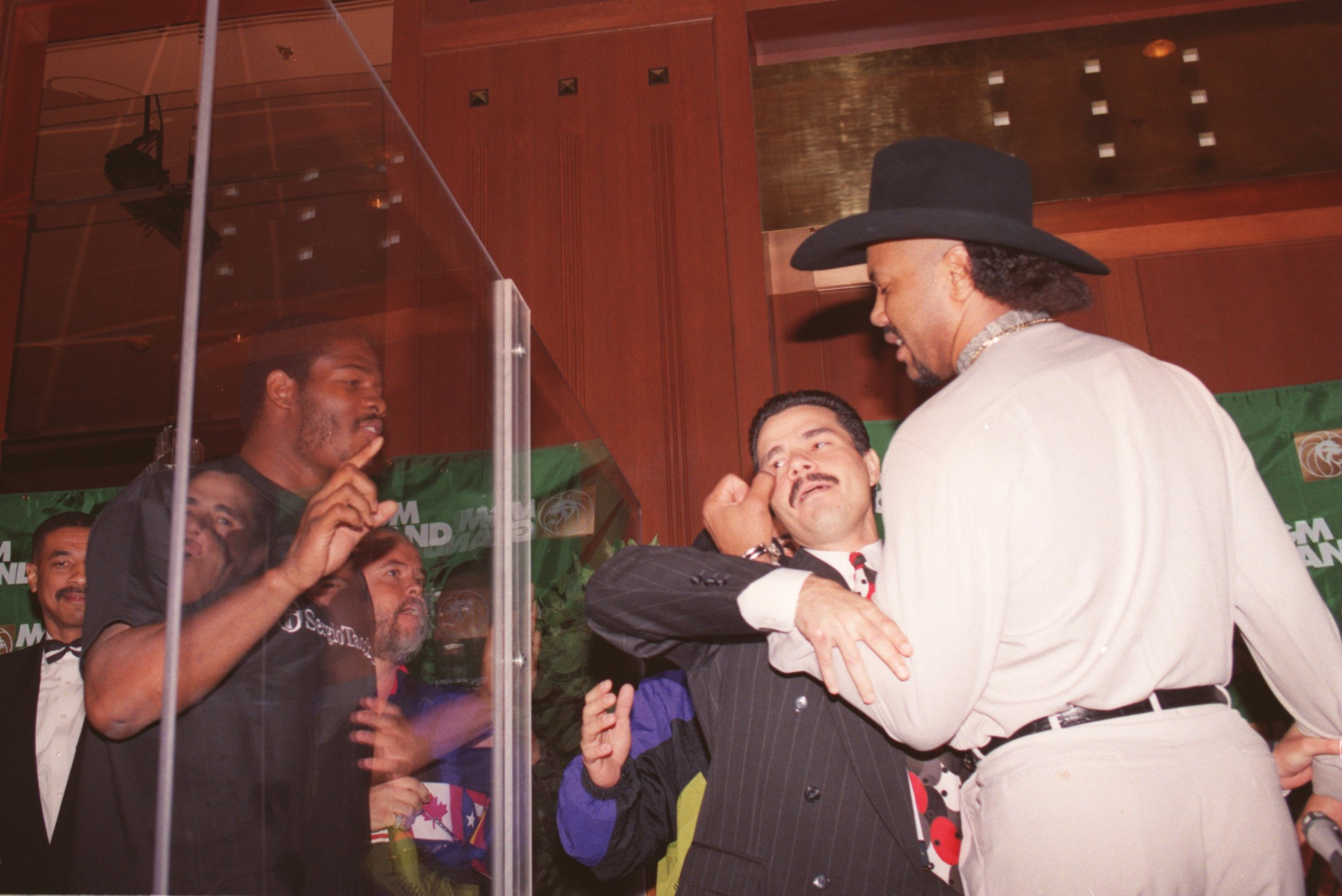 8 JUN 1995: JORGE LUIS GONZALEZ (RIGHT) IS RESTRAINED BY MANAGER LUIS DECUBAS WHILE RIDDICK BOWE (LEFT, POINTING) AND HIS MANAGER ROCK NEWMAN LOOK THROUGH THE GLASS PARTITION THAT SEPARATED THE TWO FIGHTERS DURING A PRESS CONFERENCE IN LOS ANGELES PROMOTIN THEIR UPCOMING JUNE 17 FIGHT AT THE MGM GRAND IN LAS VEGAS.