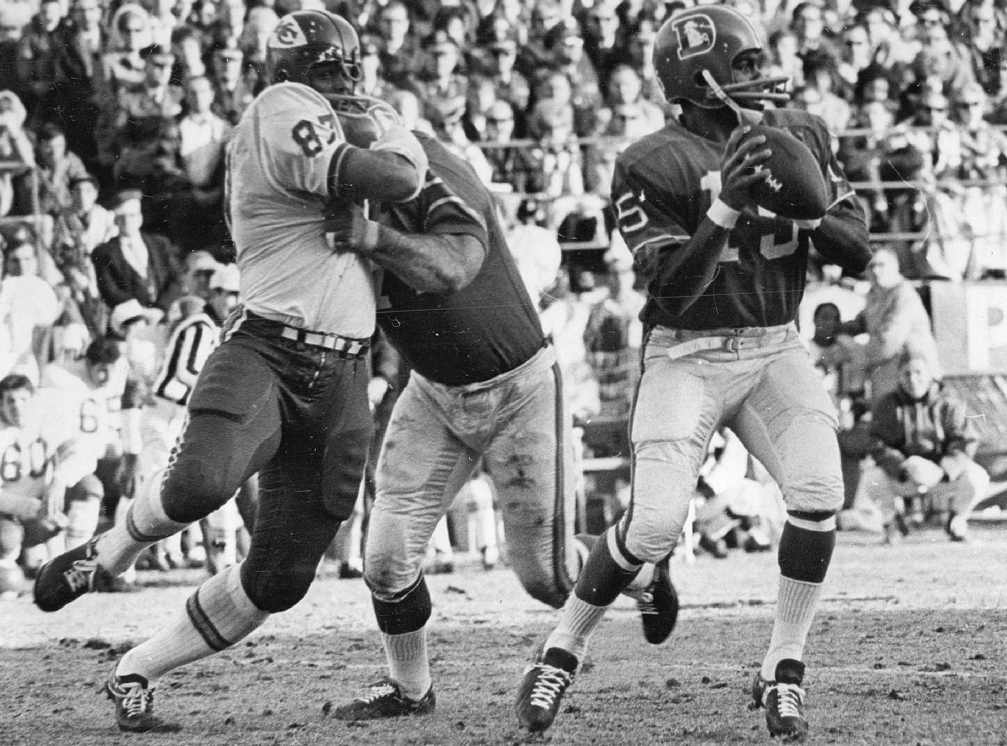 Denver quarterback Marlin Briscoe is unaware that a battle is occurring behind him in the first quarter Saturday. Denver's Sam Brunelli is shown holding Kansas City's Aaron Brown while Briscoe prepares to let loose with a pass..