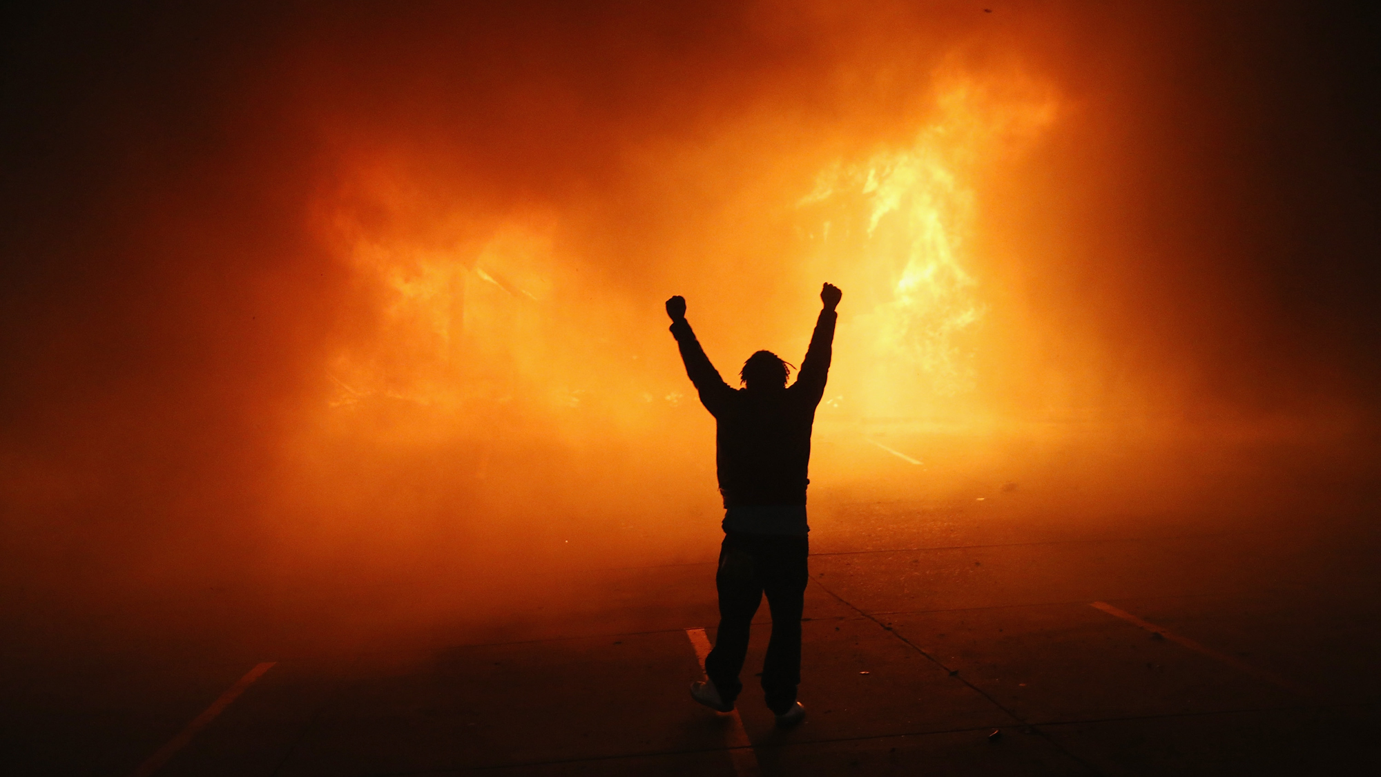 A demonstrator celebrates as a business burns after it was set on fire during rioting following the grand jury announcement in the Michael Brown case on November 24, 2014 in Ferguson, Missouri.