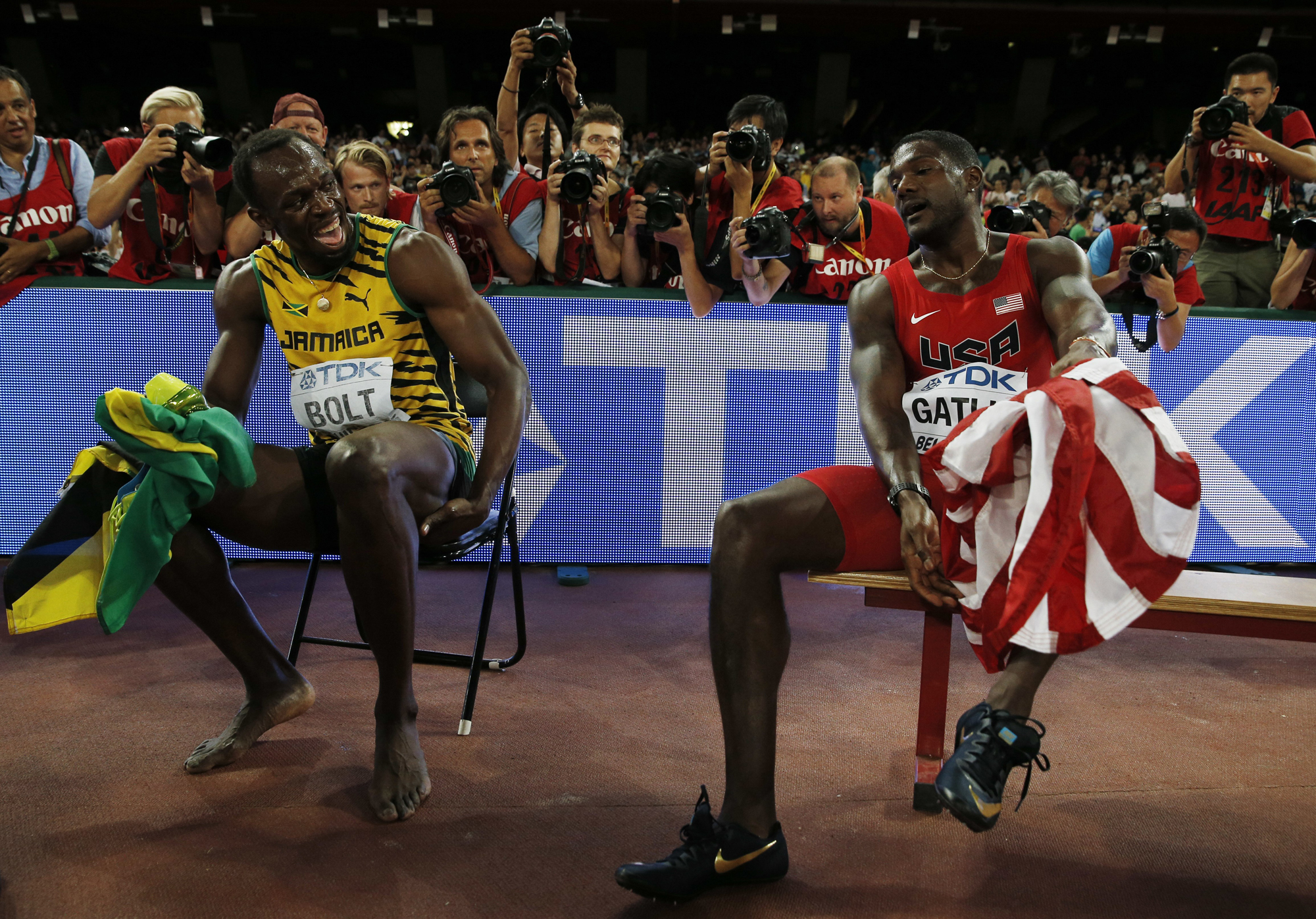 "Jamaica's Usain Bolt (L) and USA's Justin Gatlin (R) celebrate after winning first and second place respectively in the final of the men's 200 metres athletics event at the 2015 IAAF World Championships at the ""Bird's Nest"" National Stadium in Beijing on August 27, 2015."