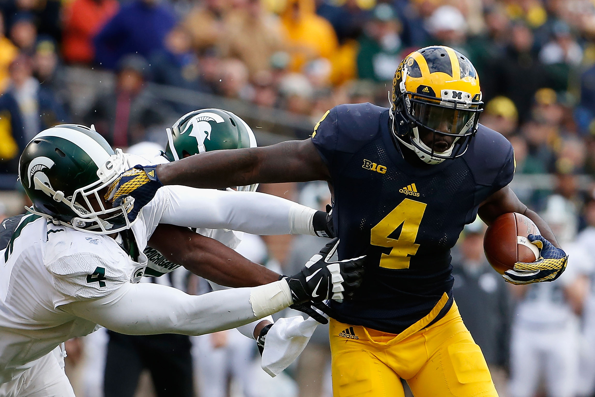 Running back De'Veon Smith #4 of the Michigan Wolverines runs with the football during the college football game against the Michigan State Spartans at Michigan Stadium on October 17, 2015 in Ann Arbor, Michigan. The Spartans defeated the Wolverines 27-23.