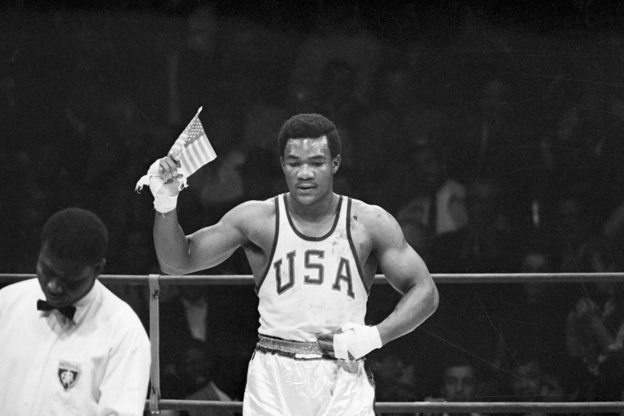 George Foreman of Houston, TX, waves a small American flag after he won the Olympics heavyweight boxing gold medal to climax America's greatest effort at an Olympics. The US walked away with 45 gold medals, 27 silvers and 34 bronze. Foreman scored a second-round technical knockout over Ionas Chepulis of the Soviet Union.