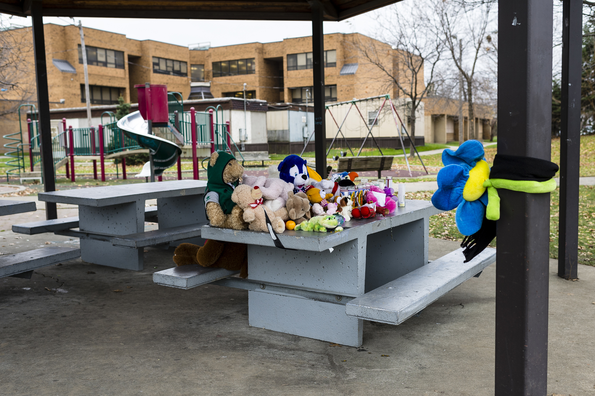 "Mourners covered a park table at the Cudell Commons Park with stuffed animals, prayer candles, and letters for 12-year old Tamir Rice in Cleveland, Ohio, on Tuesday, November 25, 2014. Rice died the previous weekend after being shot by a Cleveland police officer responding to a 911 call about a ""male threatening people with a gun."""