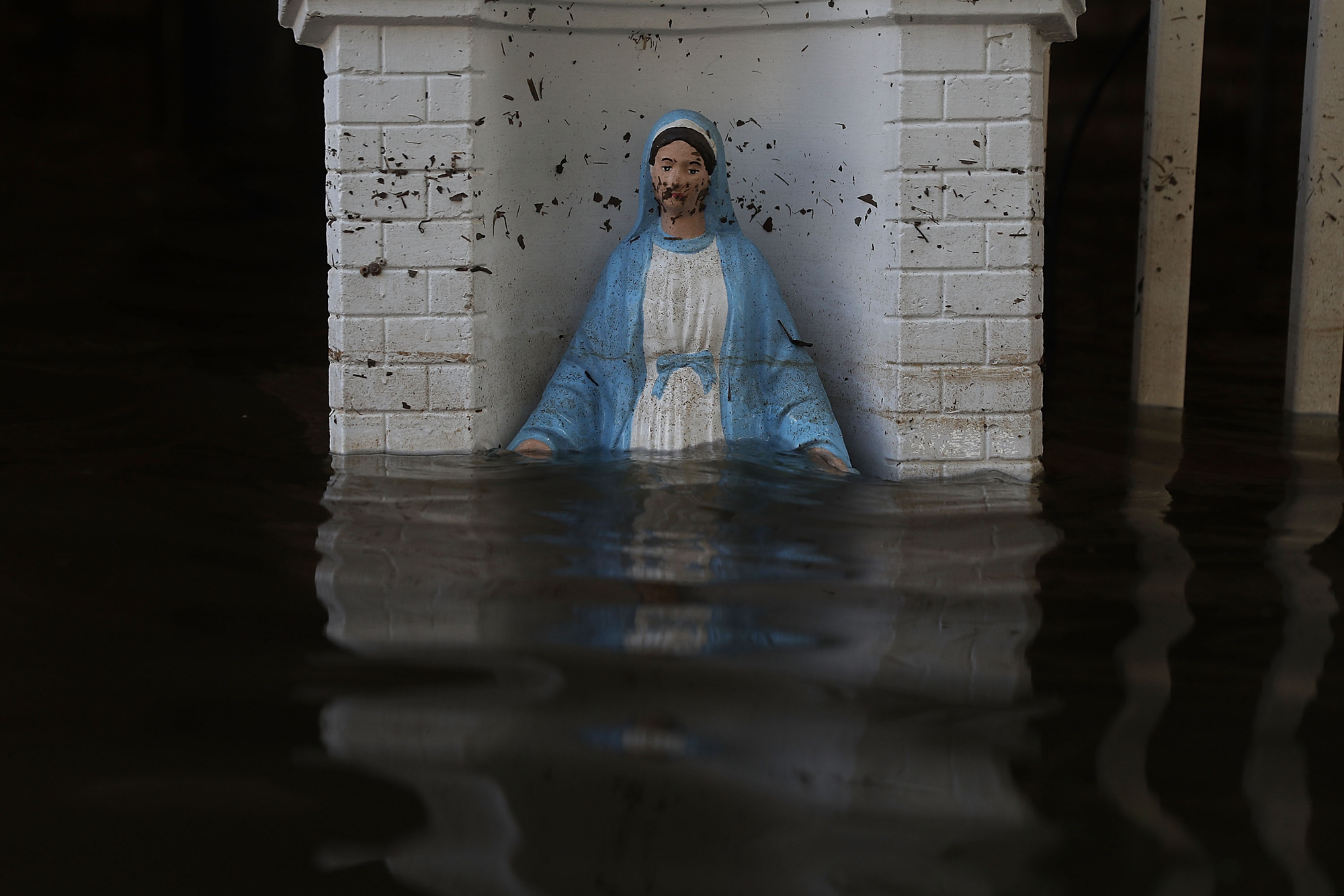 A Virgin Mary statue is seen in front of a flooded home on August 18, 2016 in St Amant, Louisiana. Last week Louisiana was overwhelmed with flood water causing at least thirteen deaths and thousands of homes damaged by the flood waters.