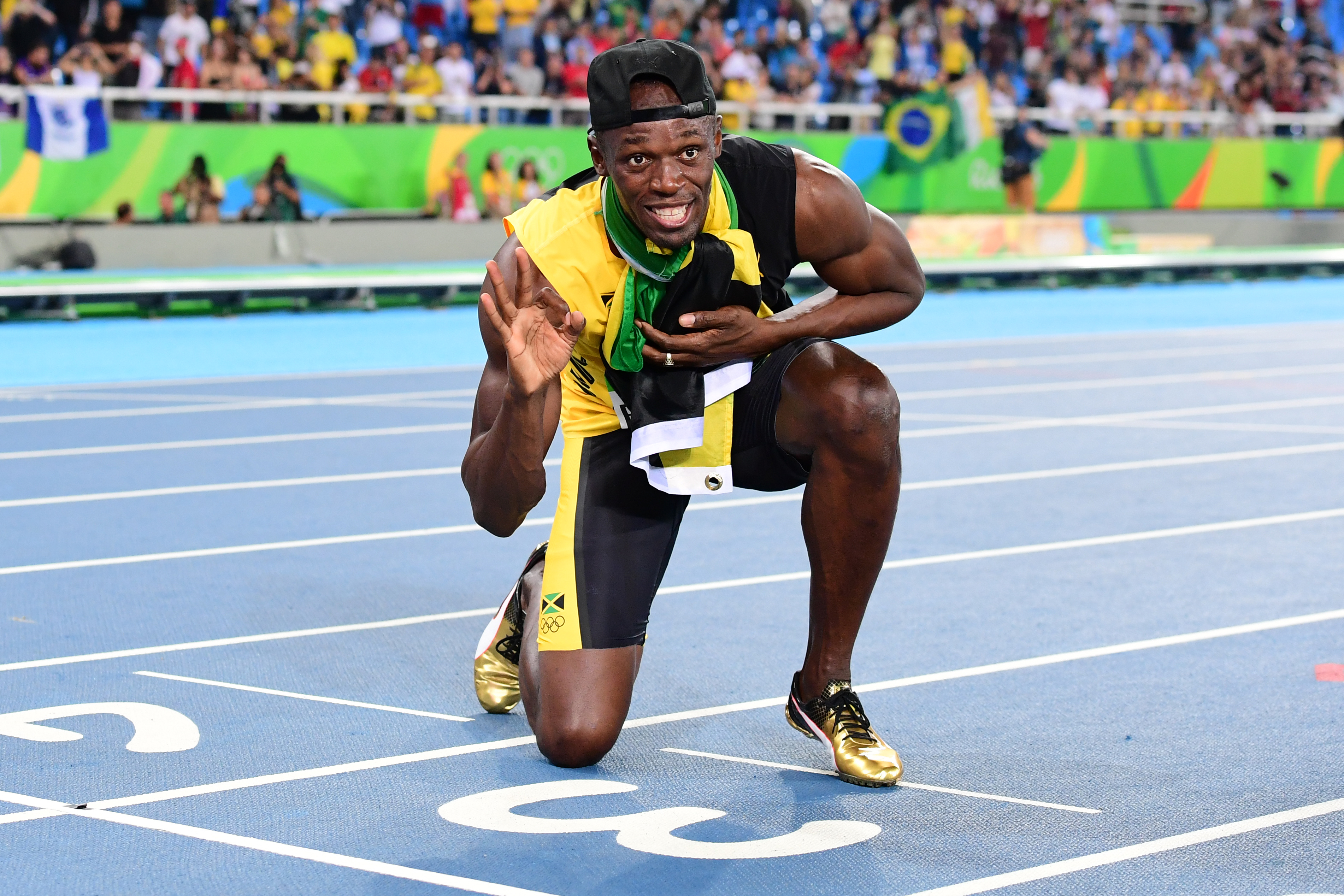 Jamaica's Usain Bolt holds up three fingers for a third relay Olympic title after Team Jamaica won the Men's 4x100m Relay Final during the athletics event at the Rio 2016 Olympic Games at the Olympic Stadium in Rio de Janeiro on August 19, 2016.