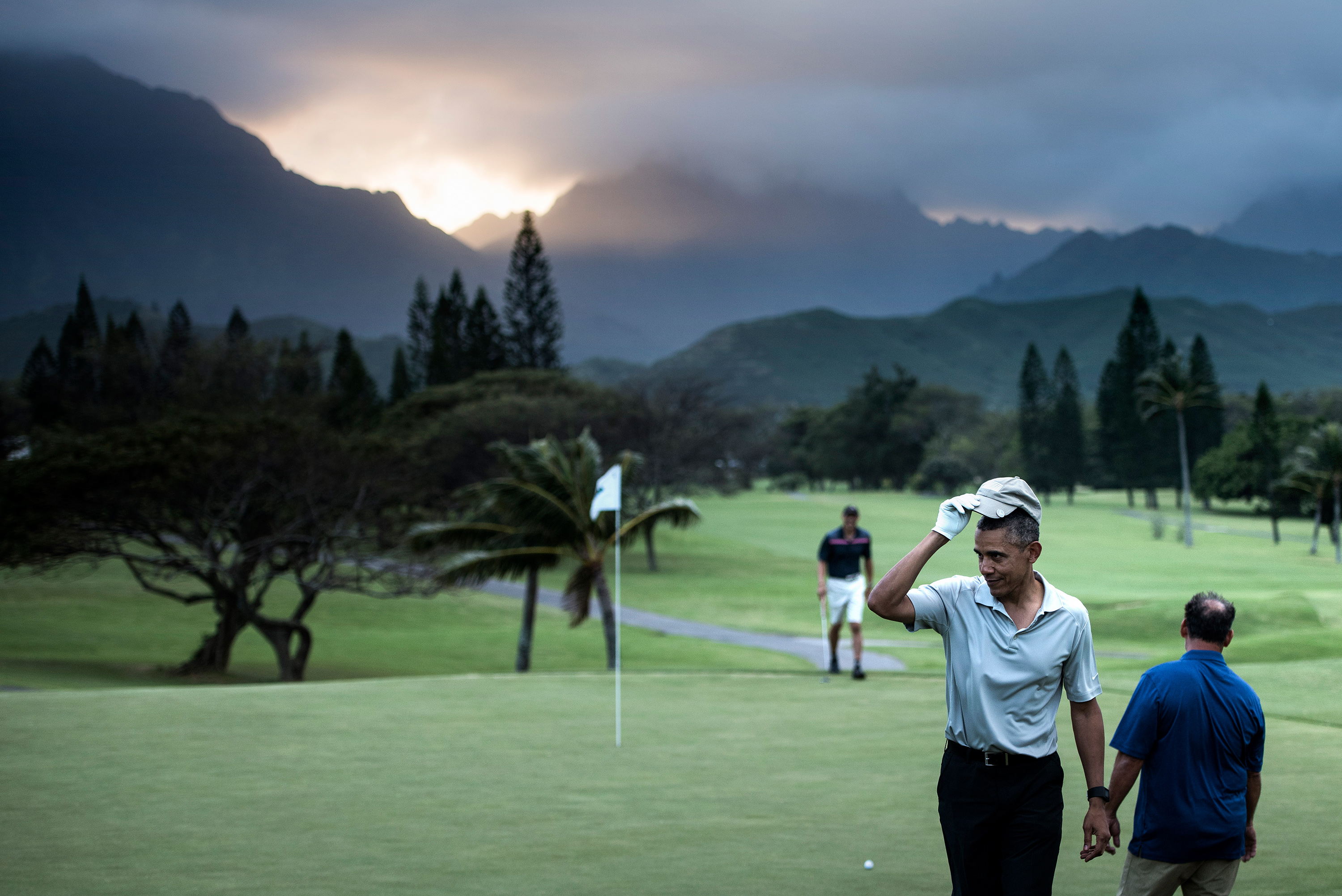 US President Barack Obama tips his hat to onlookers after chipping a ball in on the 18th green21 of the Mid-Pacific Country Club's golf course December 21, 2015 in Kailua, Hawaii. Obama and the First Family are in Hawaii for vacation.