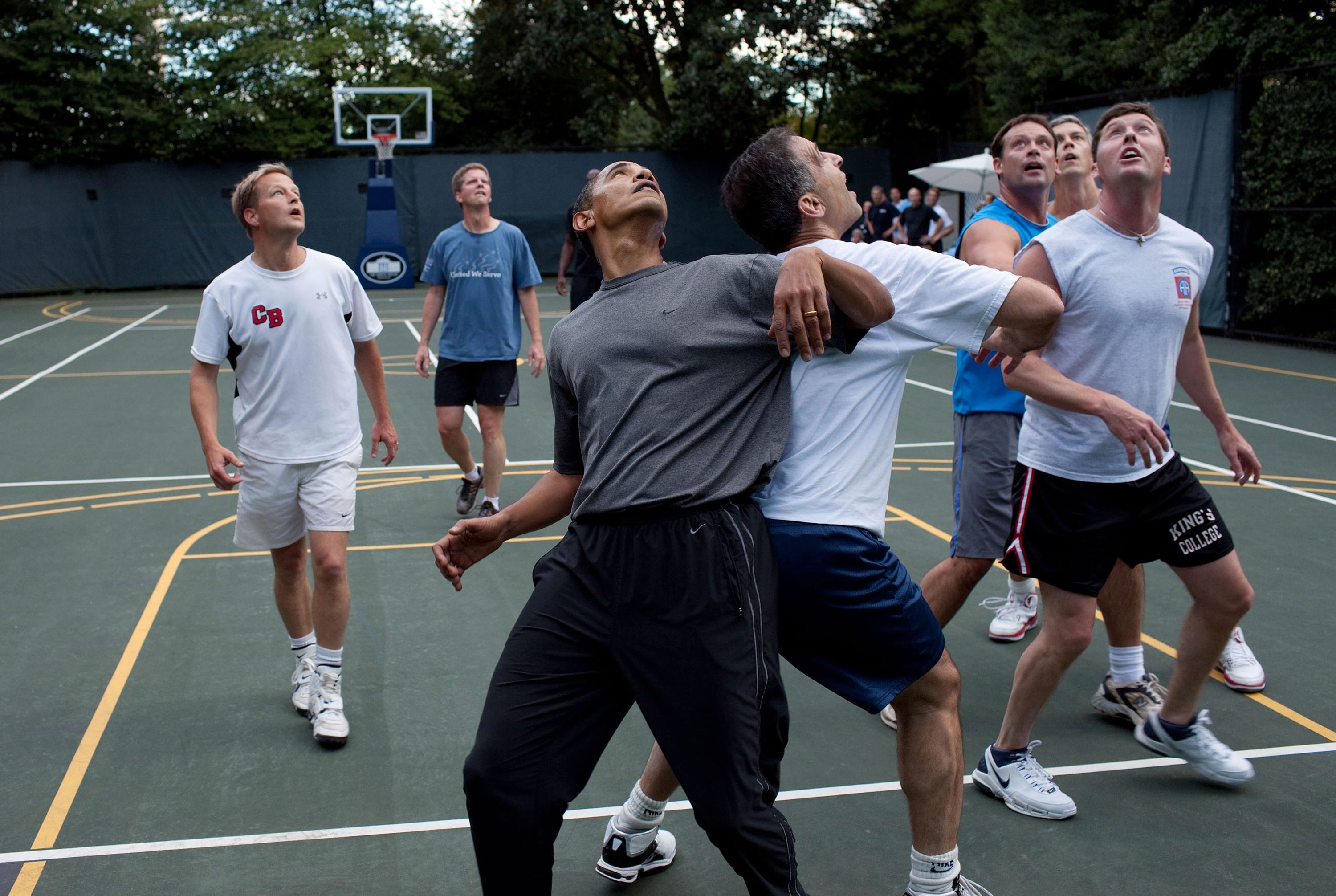 President Barack Obama, along with Cabinet Secretaries and Members of Congress, watch a shot during a basketball game on the White House court, Oct. 8, 2009.
