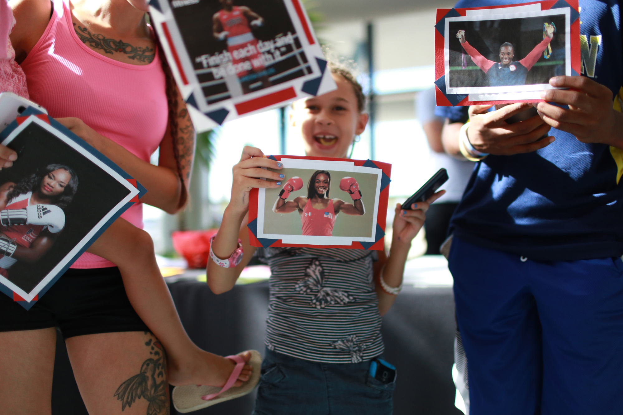 Alanah Jankowiak, 7, of Flint, Mich., holds a photo of Olympic gold medalist Claressa Shields with her family members while waiting to greet her at Bishop International Airport in Flint on Tuesday, Aug. 23, 2016, as she returns home from the Olympics in Rio de Janeiro.