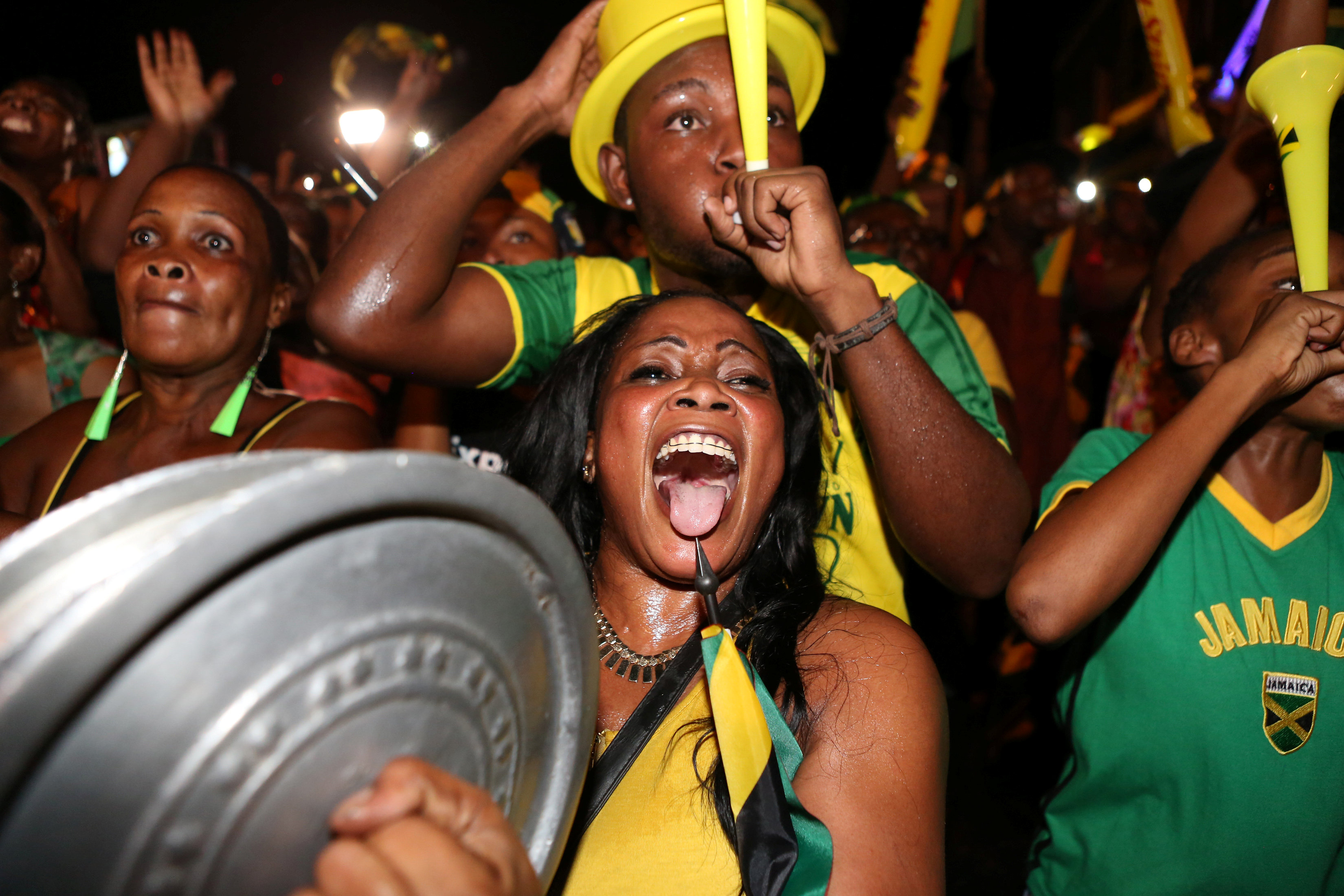 Fans cheer while watching a broadcast of Jamaica's Usain Bolt winning the men's 100 meters final and becoming the first man to win three successive Olympic titles on the track, in Kingston, Jamaica, August 14, 2016.