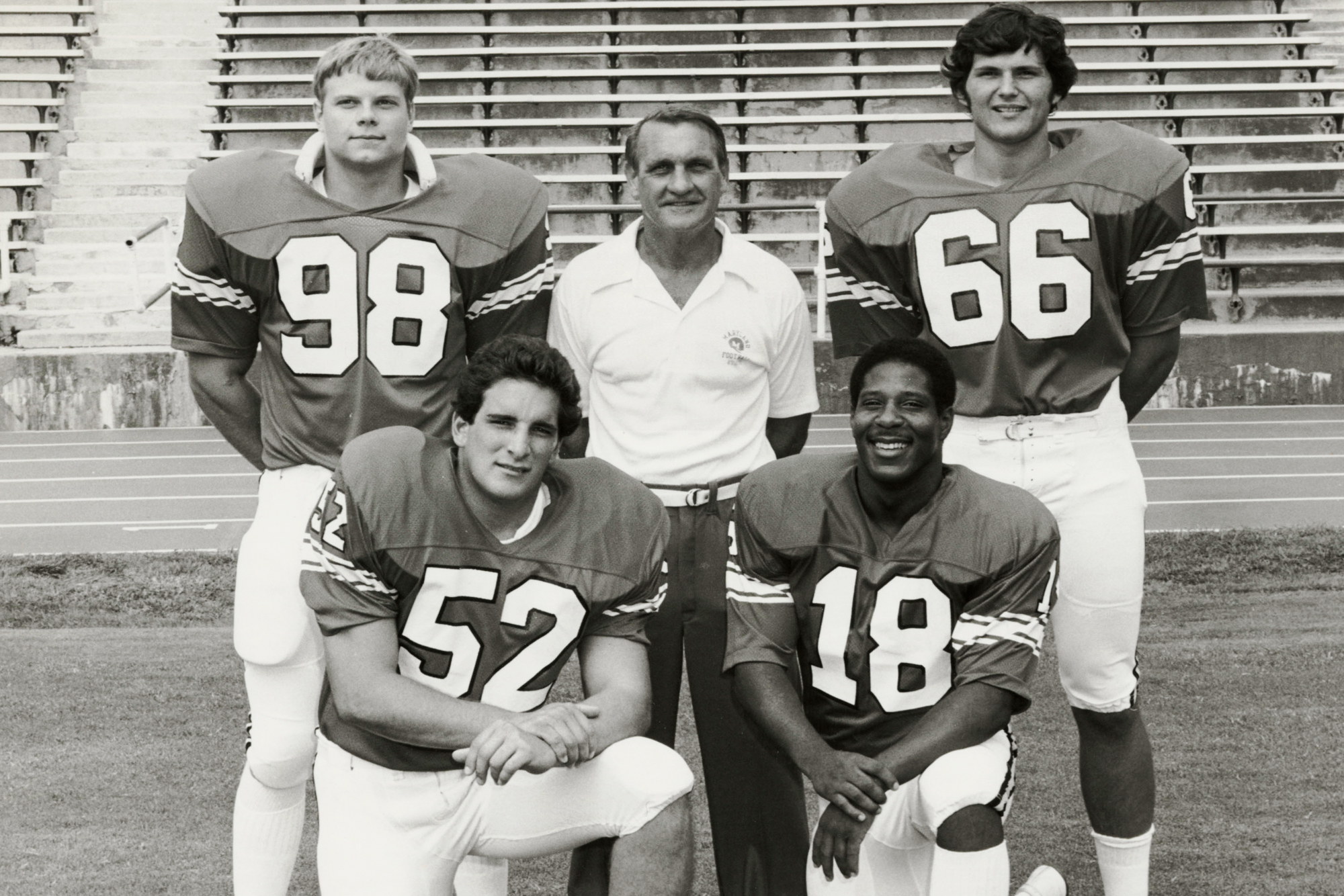 Maryland head coach Jerry Claiborne poses with Maryland football players Mark Duda (#98), Vince Tomasetti (#52), Charlie Wysocki (#18), and Ron Solt (#66).