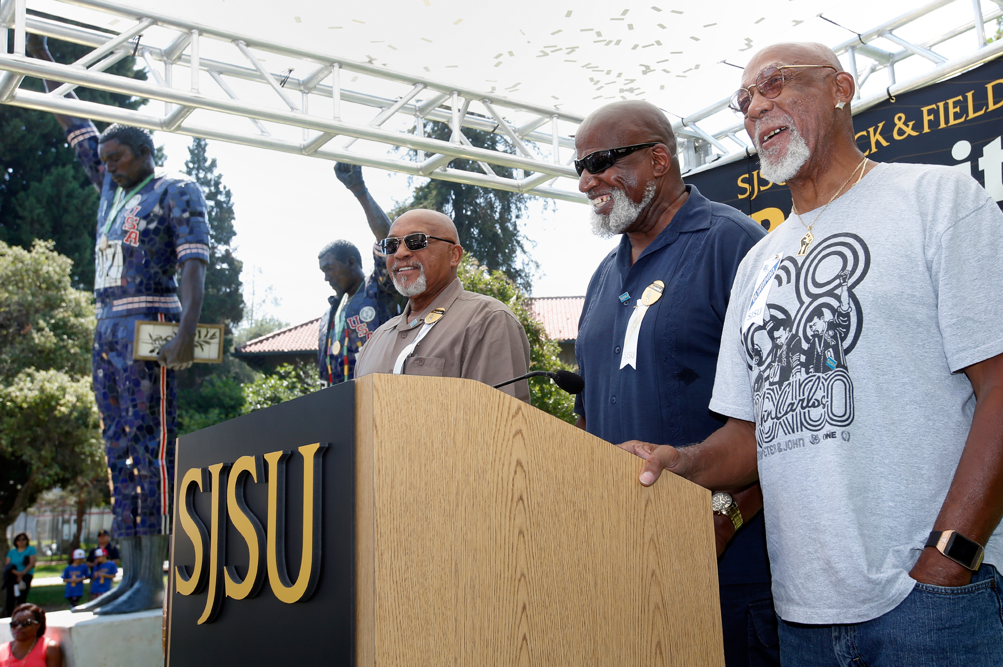 Sociology professor Harry Edwards stands between Spartan track star Tommie Smith, left, and John Carlos, as San Jose State University announces the return of the track and field program Monday, Aug. 1, 2016. The announcement was made next to the 24-foot-tall statutes of the two track stars famous '68 Olympics salute.