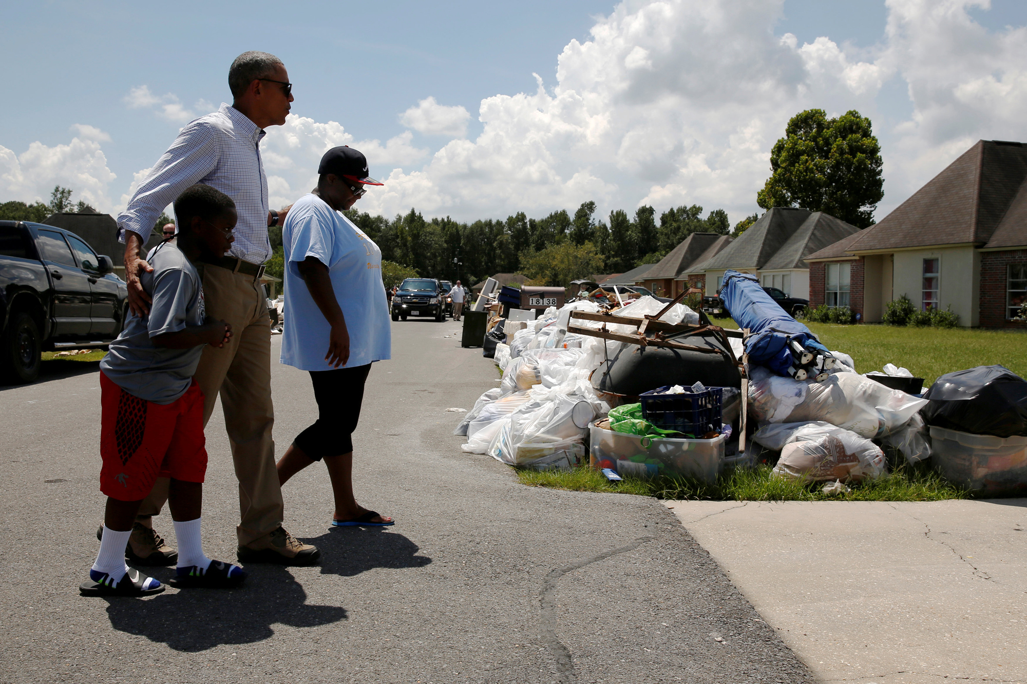 U.S. President Barack Obama greets a family as he tours houses in a flood-affected neighborhood in Zachary