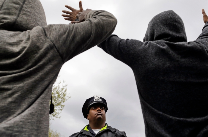 A member of the Baltimore Police Department stands guard outside of the department's Western District police station as men hold their hands up in protest during a march for Freddie Gray, Wednesday, April 22, 2015, in Baltimore.