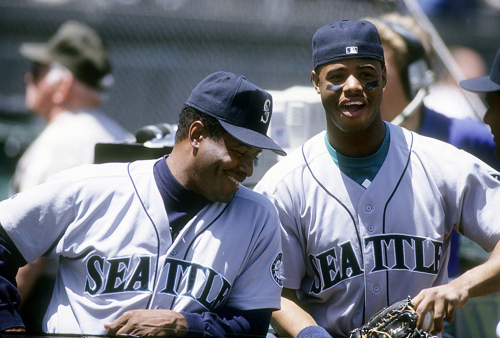 Outfielders Ken Griffey Jr. #24 (R) and coach Ken Griffey Sr. (L) of the Seattle Mariners laugh together circa 1993 before the start of a Major League Baseball game against the Oakland Athletics at the Oakland Coliseum in Oakland, California.