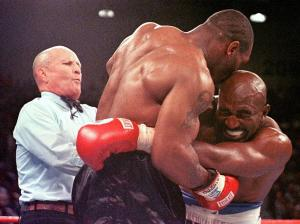 This 28 June 1997 file photo shows referee Lane Mills (L) stepping in as Evander Holyfield (R) reacts after Mike Tyson (C) bit his ear in the third round of their WBA Heavyweight Championship Fight at the MGM Grand Garden Arena in Las Vegas, NV.