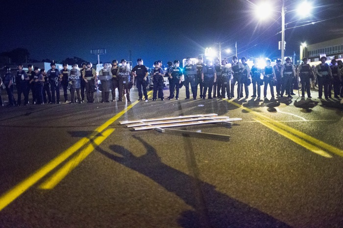 Police stand guard as demonstrators, marking the one-year anniversary of the shooting of Michael Brown, protest along West Florrisant Street on August 10, 2015 in Ferguson, Missouri.