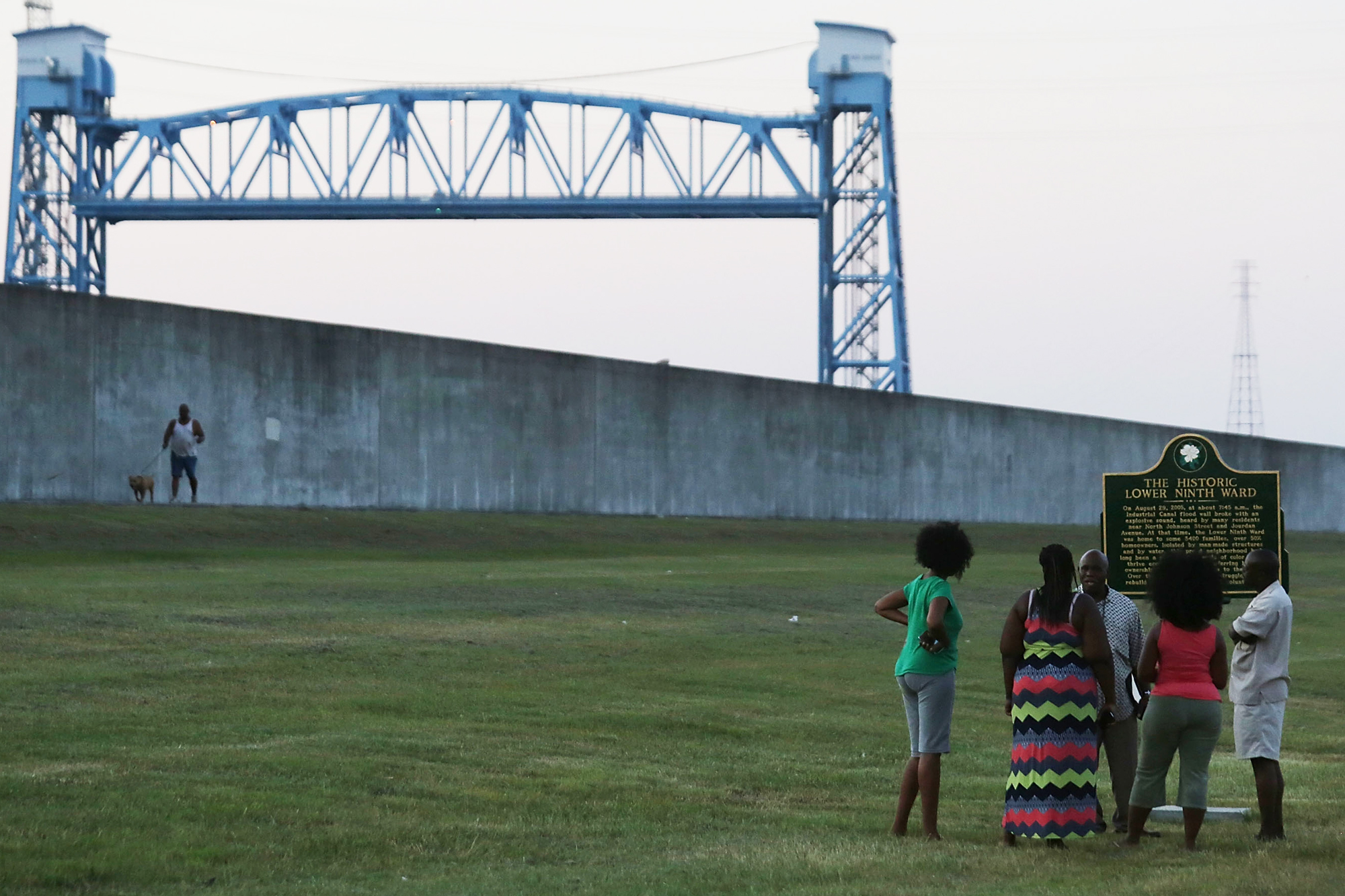 People visit the newly erected historic marker at the site where the Lower Ninth Ward levee failed on August 27, 2015 in New Orleans, Louisiana. The new levee stands in the background.