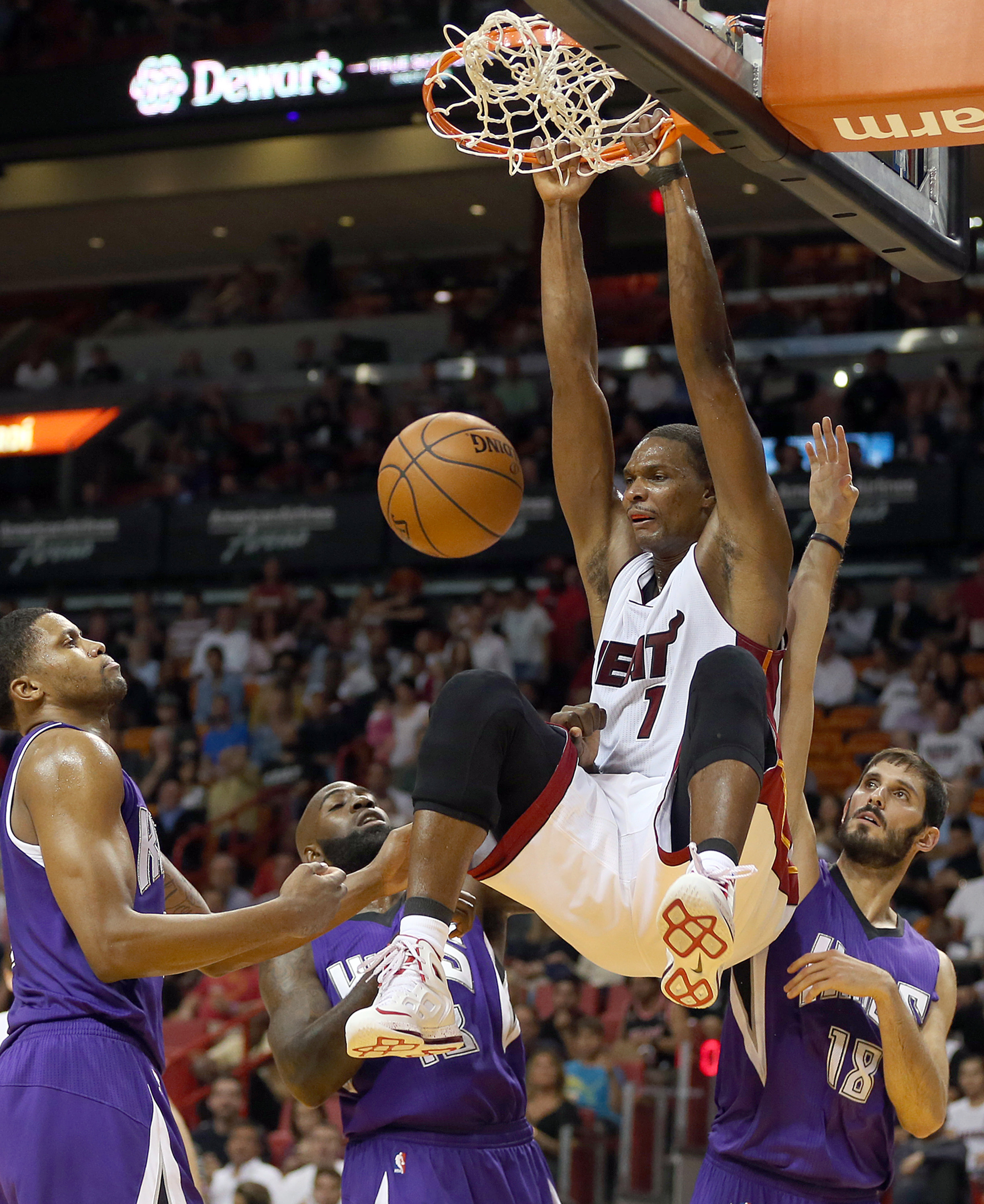 The Miami Heat's Chris Bosh dunks against the Sacramento Kings', from left, Rudy Gay, Quincy Acy, and Omri Cassp, in the second quarter at AmericanAirlines Arena in Miami on Thursday, Nov. 19, 2015.