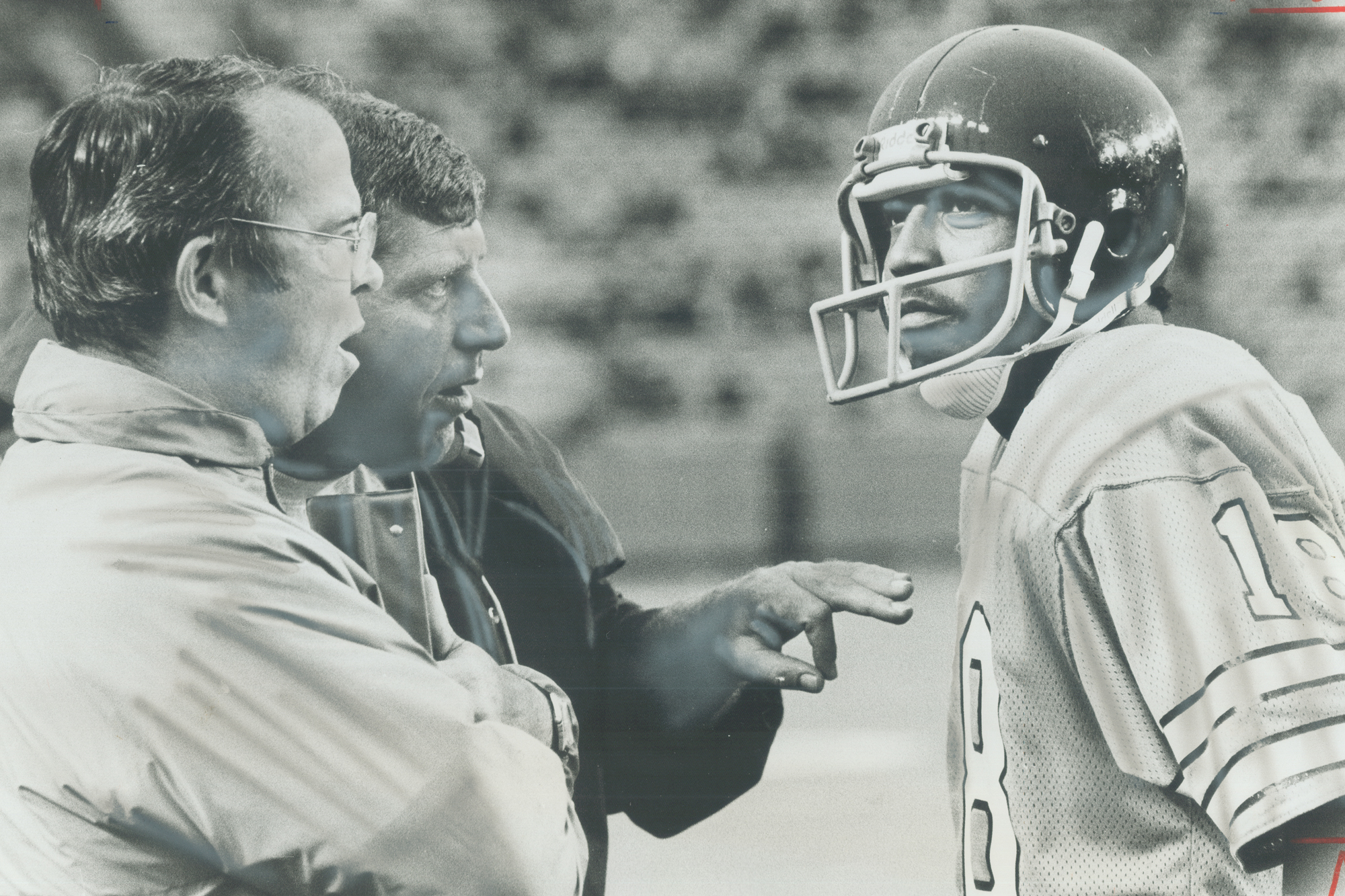 Toronto Argonaut head coach Leo Cahill (1) and assistant coach Chuck Dickerson (middle) speak with quarterback Chuck Ealey during final exhibition game against Ottawa Rough Riders.