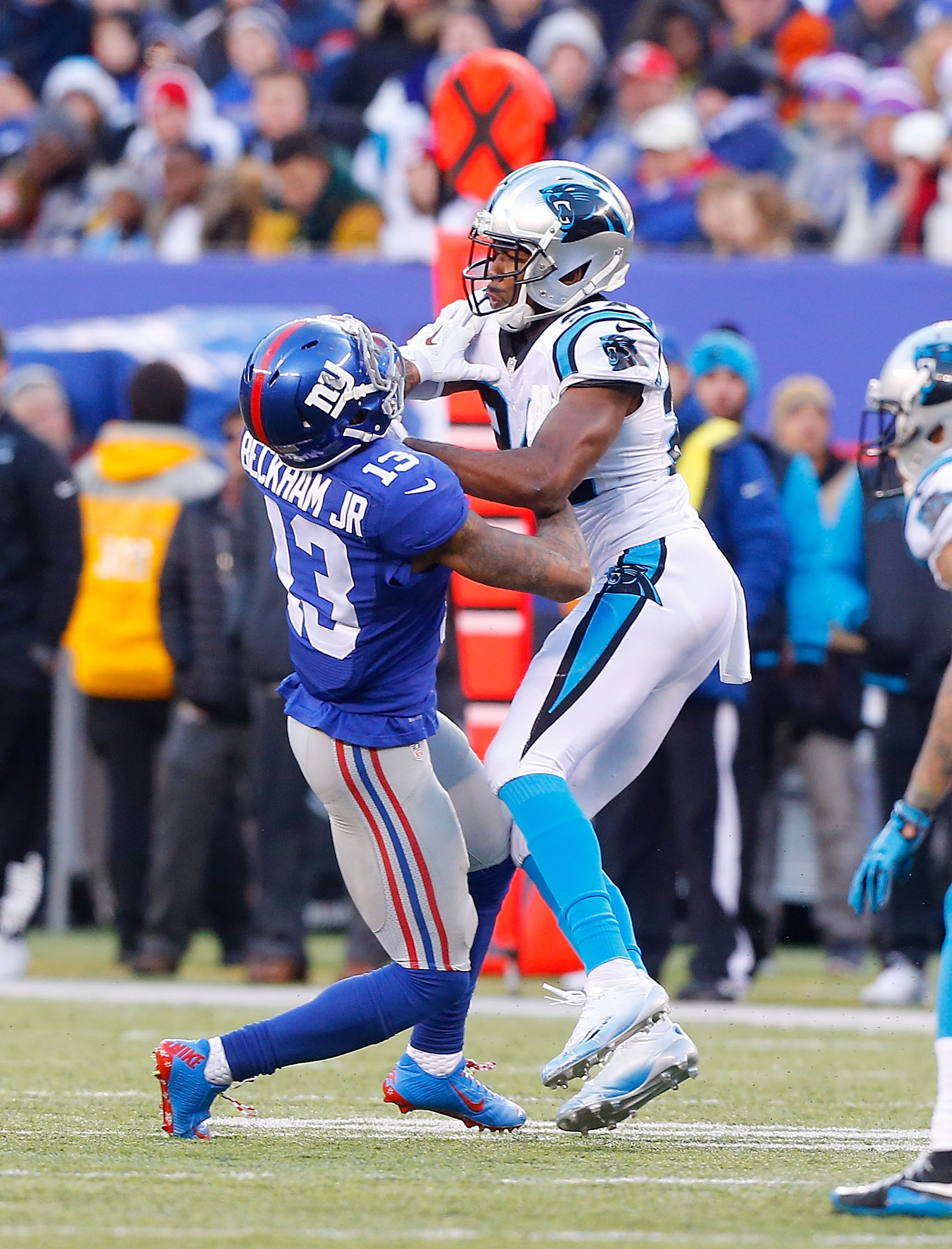EAST RUTHERFORD, NJ - DECEMBER 20: (NEW YORK DAILIES OUT) Odell Beckham #13 of the New York Giants is hit by Josh Norman #24 of the Carolina Panthers during the second half on December 20, 2015 at MetLife Stadium in East Rutherford, New Jersey. The Panthers defeated the Giants 38-35.