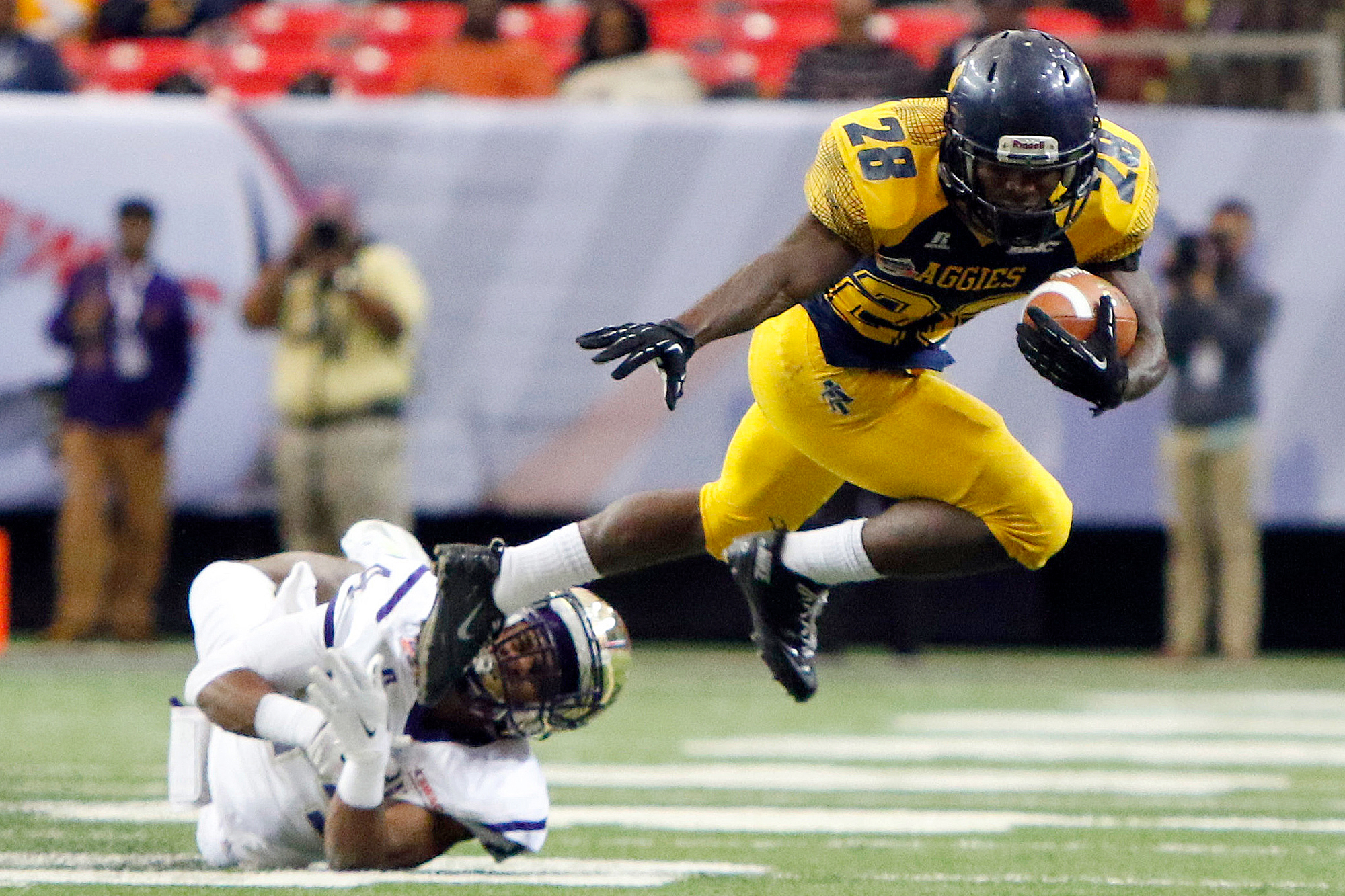 North Carolina A&T Aggies running back Tarik Cohen (28) is tackled by Alcorn State Braves defensive back Warren Gatewood (24) in the second quarter of the 2015 Celebration Bowl at the Georgia Dome.