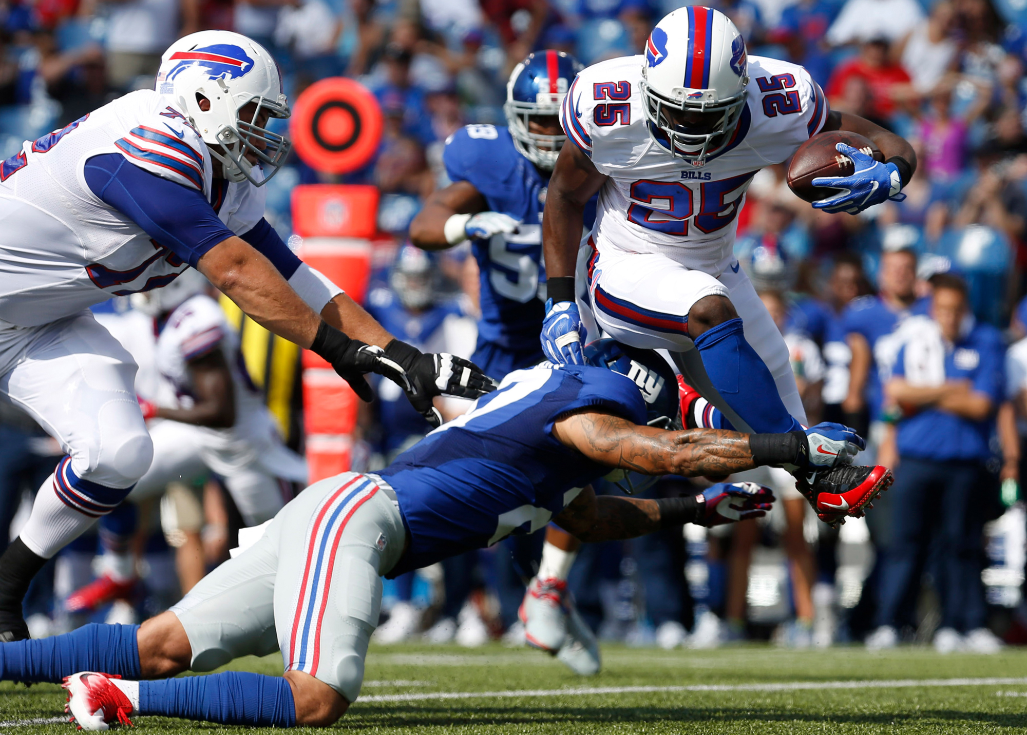 Buffalo Bills running back LeSean McCoy (25) jumps to avoid a tackle by New York Giants safety Darian Thompson (27) during the first half at New Era Field.