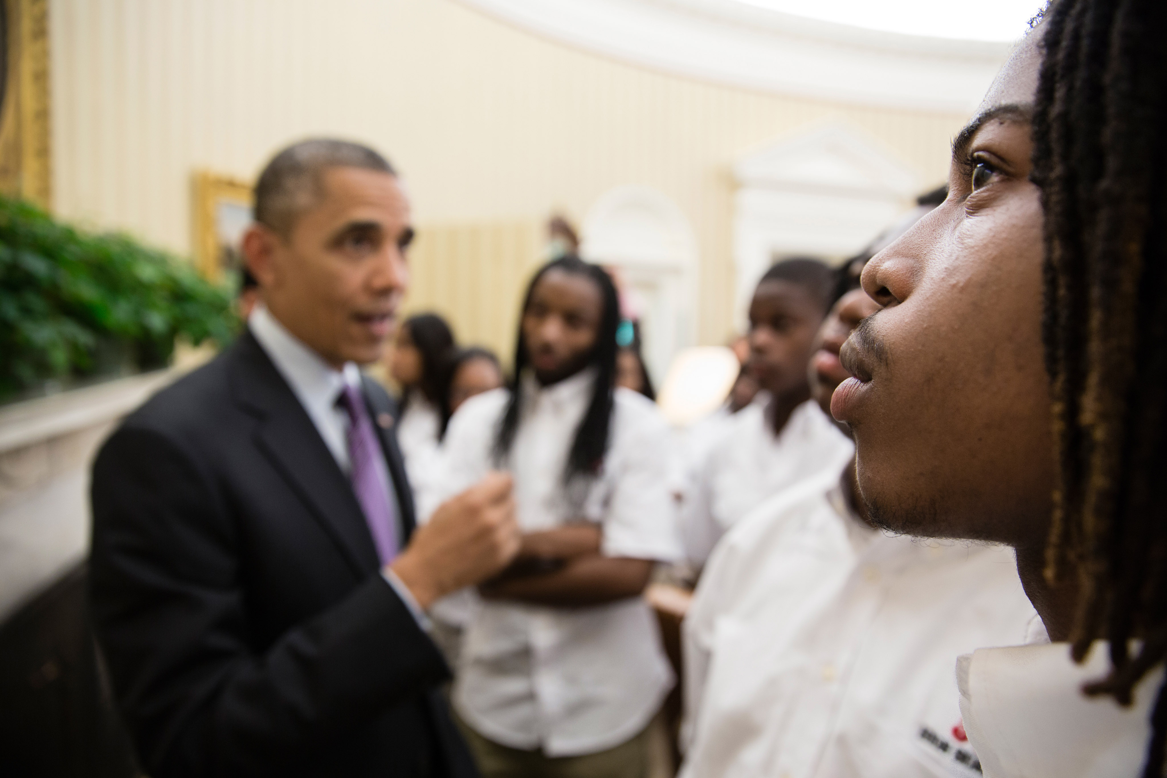 Students from William R. Harper High School in Chicago, Ill., listen as President Barack Obama talks with them about the Emancipation Proclamation hanging in the Oval Office, June 5, 2013.