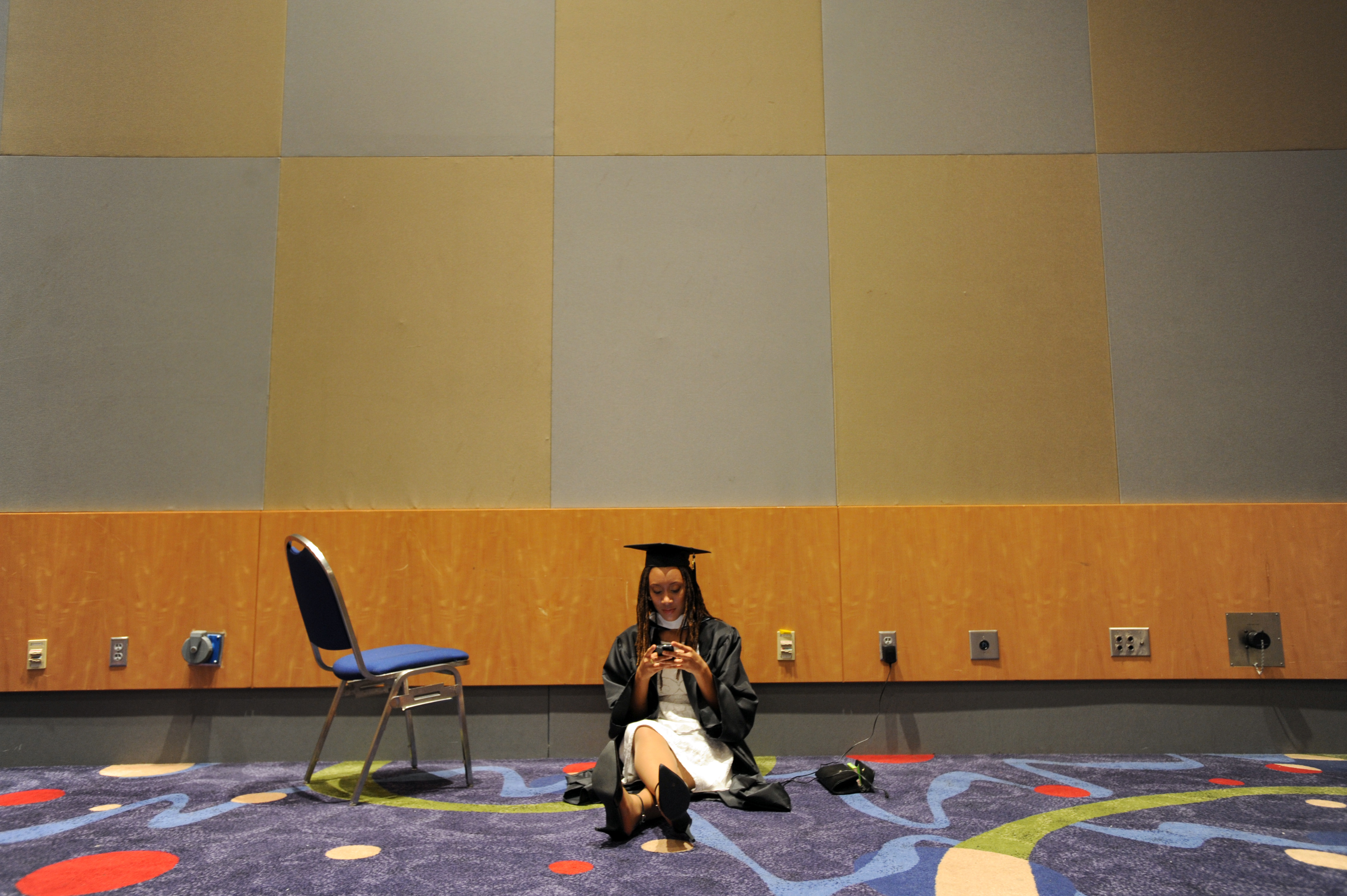 Spelman College graduating senior Vivian Aguayo, 20, of Silver Spring, Md., uses her mobile phone while waiting to participate in her commencement ceremony on Sunday, May 15, 2011, at the Georgia International Convention Center in College Park, Ga.