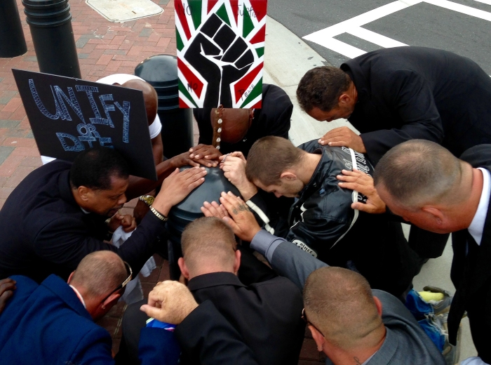 Black Lives Matter demonstrators pray and lay hands on an unidentified man outside police headquarters in Charlotte, N.C., on Tuesday, Sept. 27, 2016. The group gathered outside the building while it was shut down as authorities investigated a suspicious package following days of protests over the fatal police shooting of a black man.