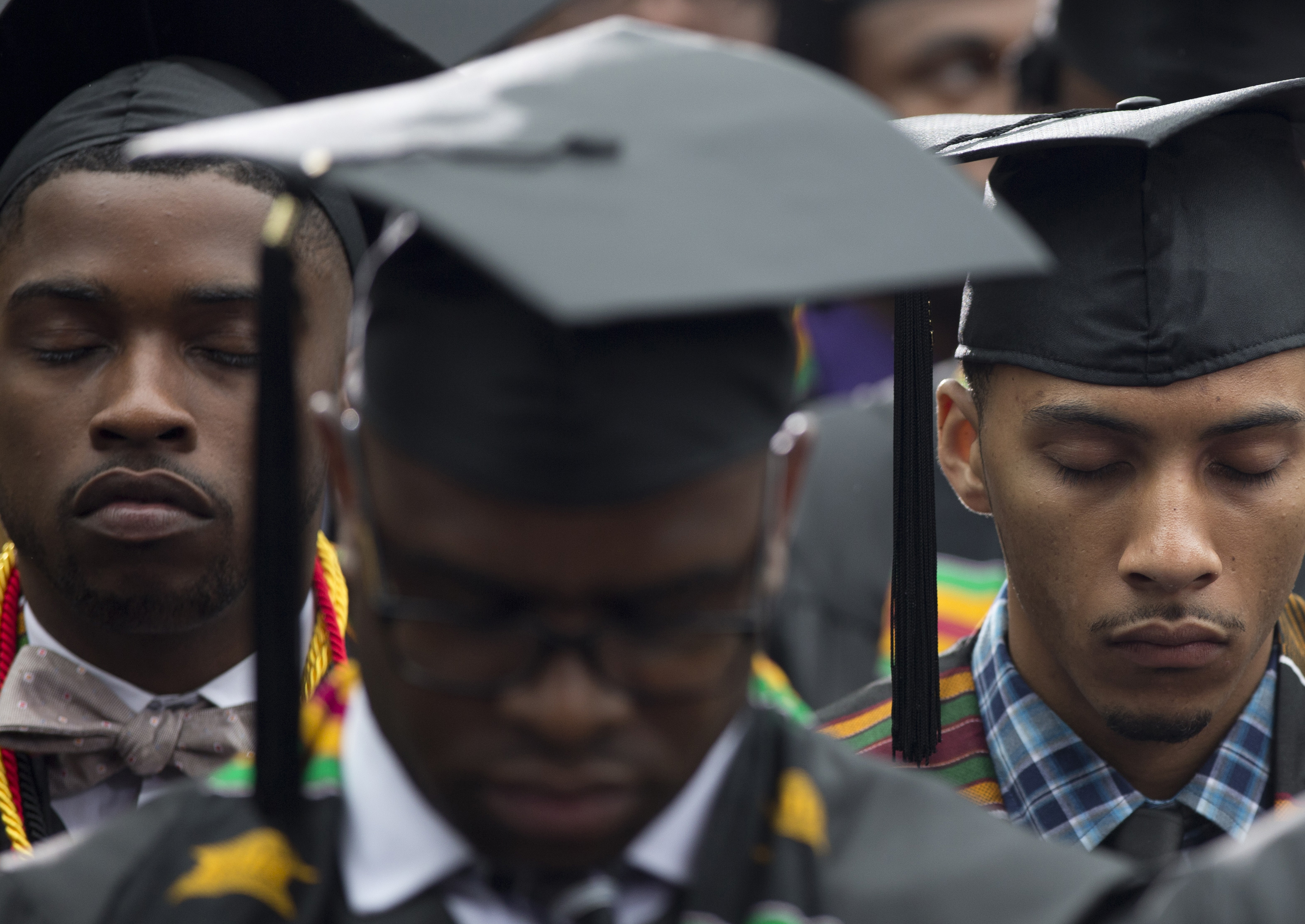 Graduates bow their heads to pray during the Morehouse College 129th Commencement ceremony, Sunday, May 19, 2013, in Atlanta, before President Barack Obama speaks.