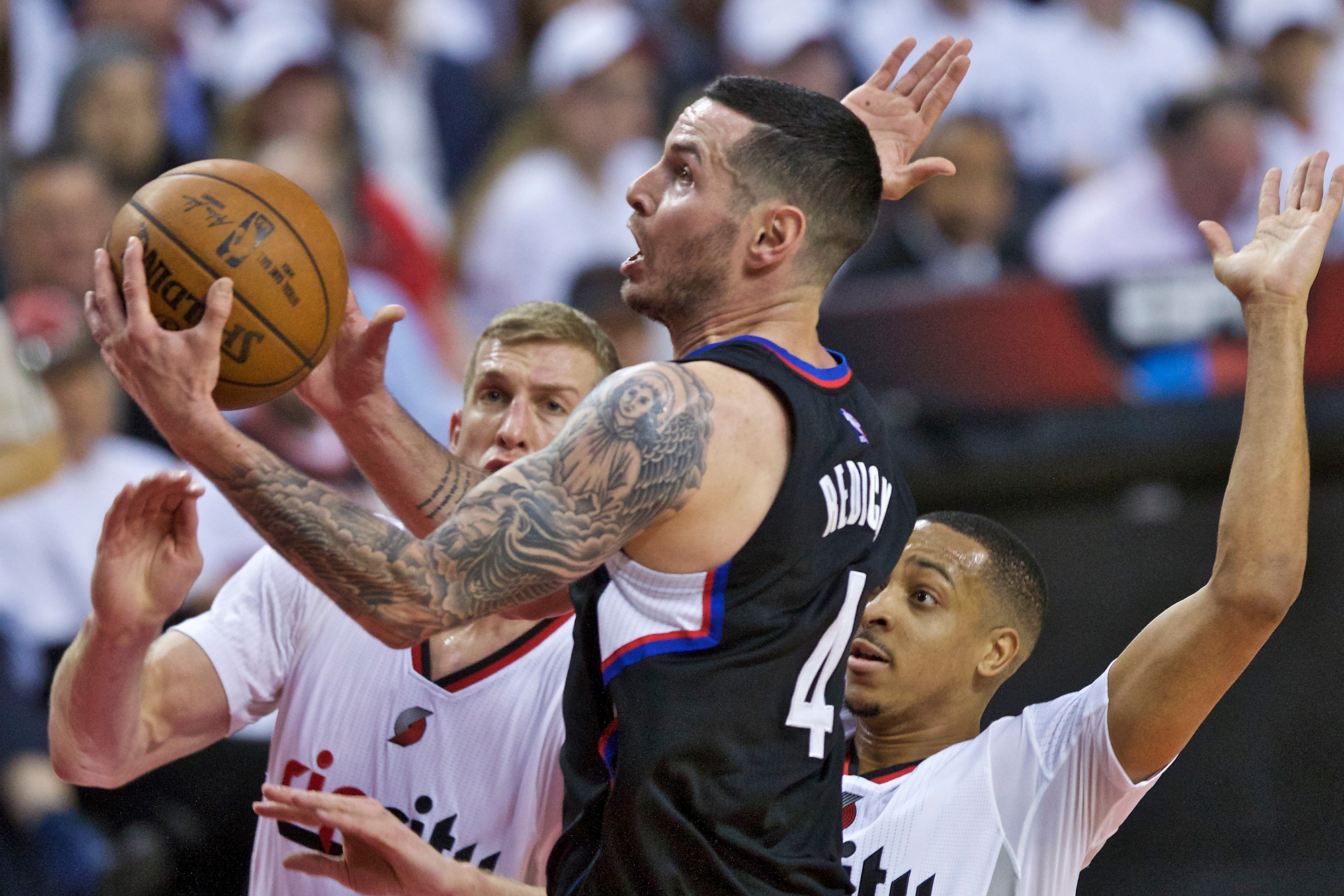 Los Angeles Clippers guard J.J. Redick, center, shoots in front of Portland Trail Blazers center Mason Plumlee, left, and guard C.J. McCollum, right, during the first half of Game 3 of an NBA basketball first-round playoff series Saturday, April 23, 2016, in Portland, Ore