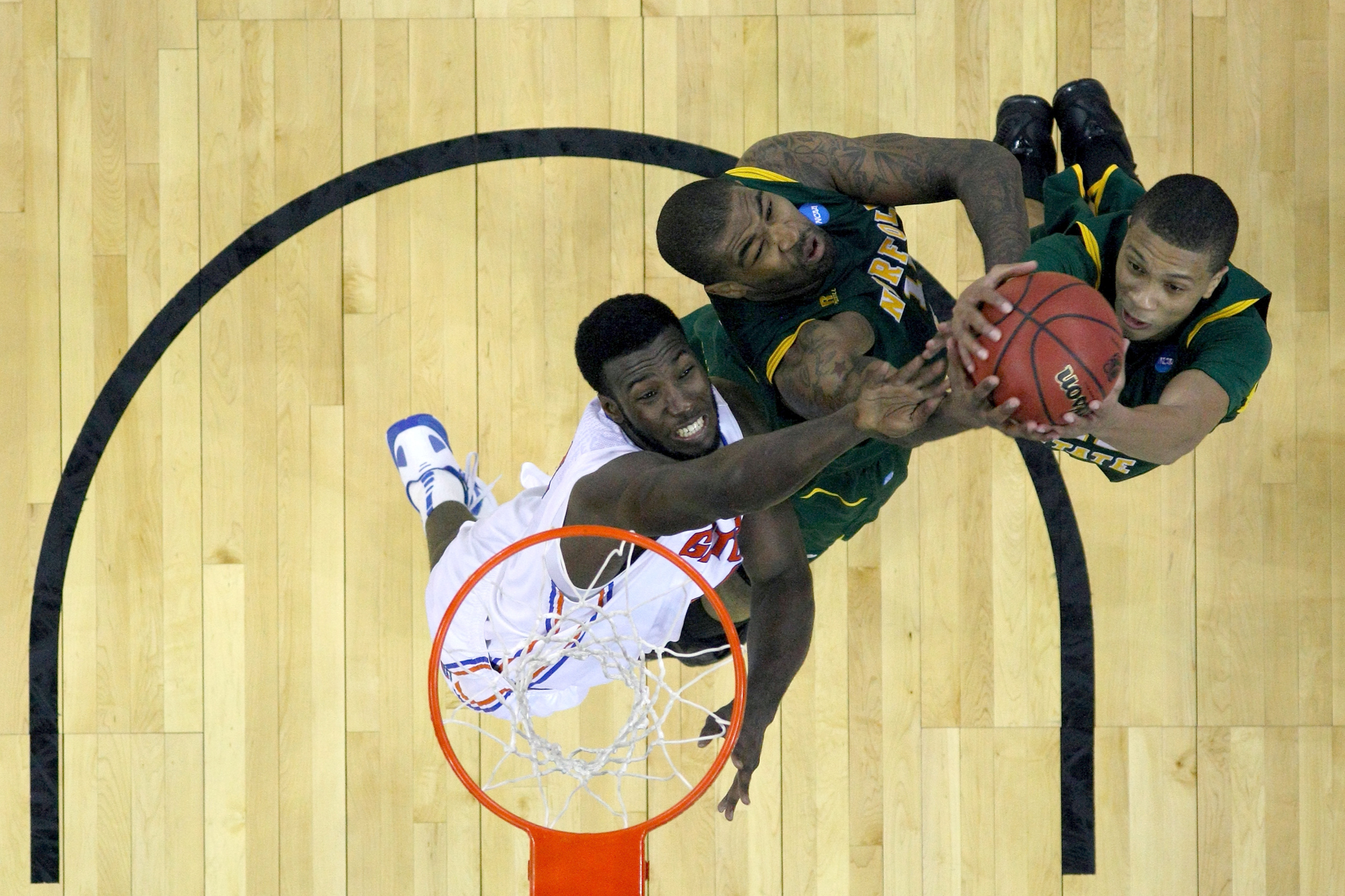 Patric Young #4 of the Florida Gators fights for a rebound against Kyle O'Quinn #10 (C) and Pendarvis Williams #11 of the Norfolk State Spartans during the third round of the 2012 NCAA Men's Basketball Tournament at CenturyLink Center on March 18, 2012 in Omaha, Nebraska.
