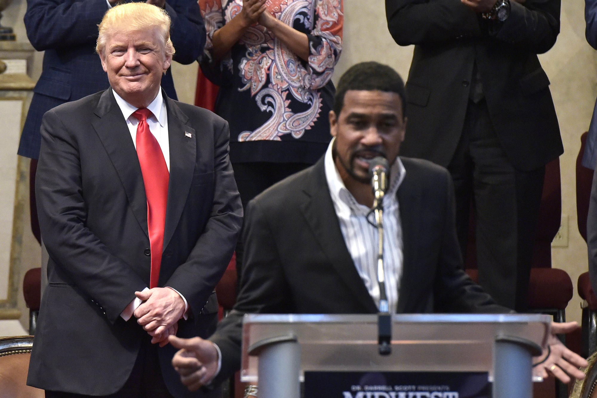 Republican presidential nominee Donald Trump (C) stands as pastor Darrell Scott (R) speaks during the Midwest Vision and Values Pastors and Leadership Conference at the New Spirit Revival Center in Cleveland Heights, Ohio on September 21, 2016.