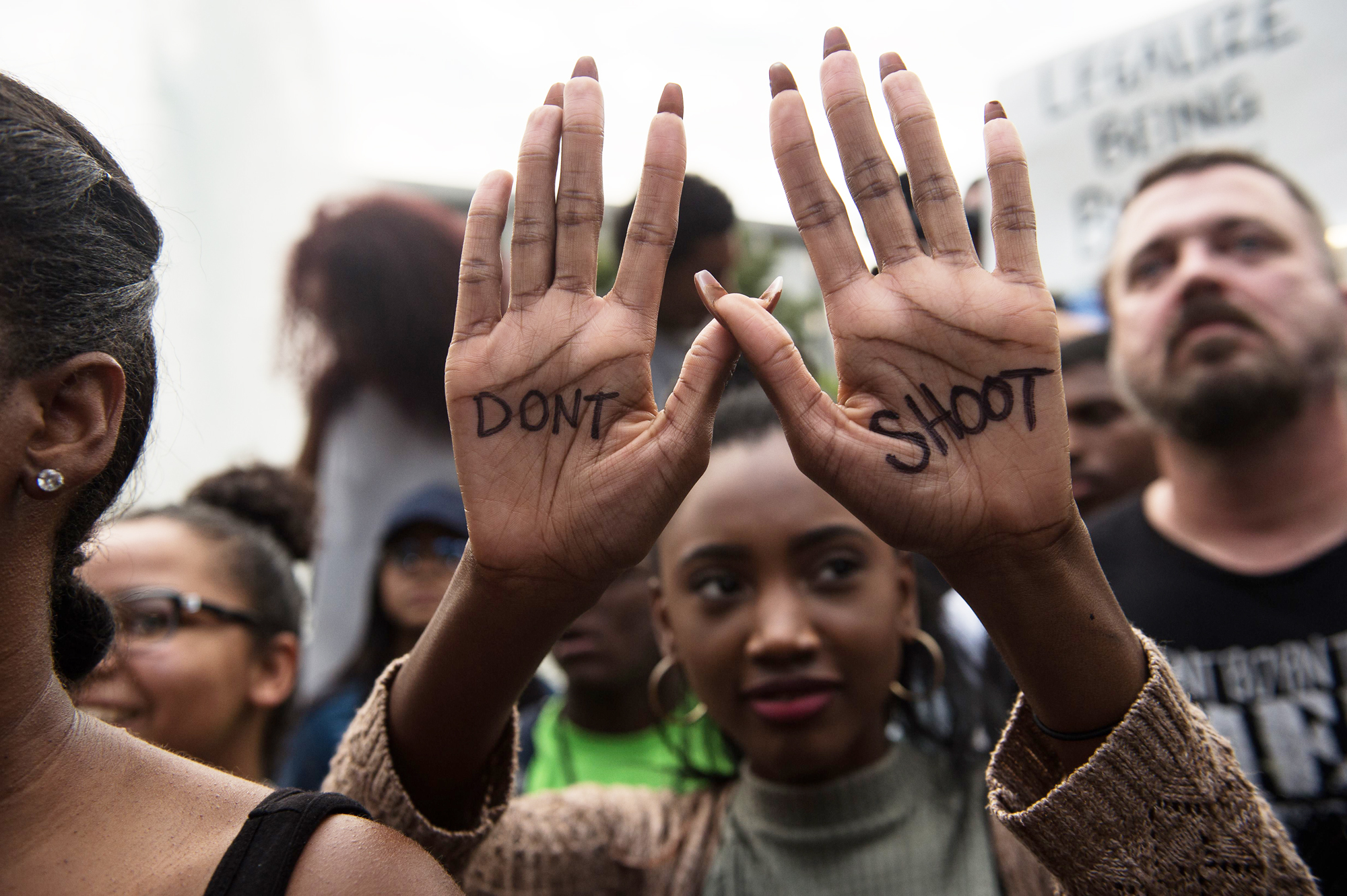 A protester holds up her hands with a slogan written on them during a demonstration against police brutality in Charlotte, North Carolina, on September 21, 2016, following the shooting of Keith Lamont Scott the previous day.