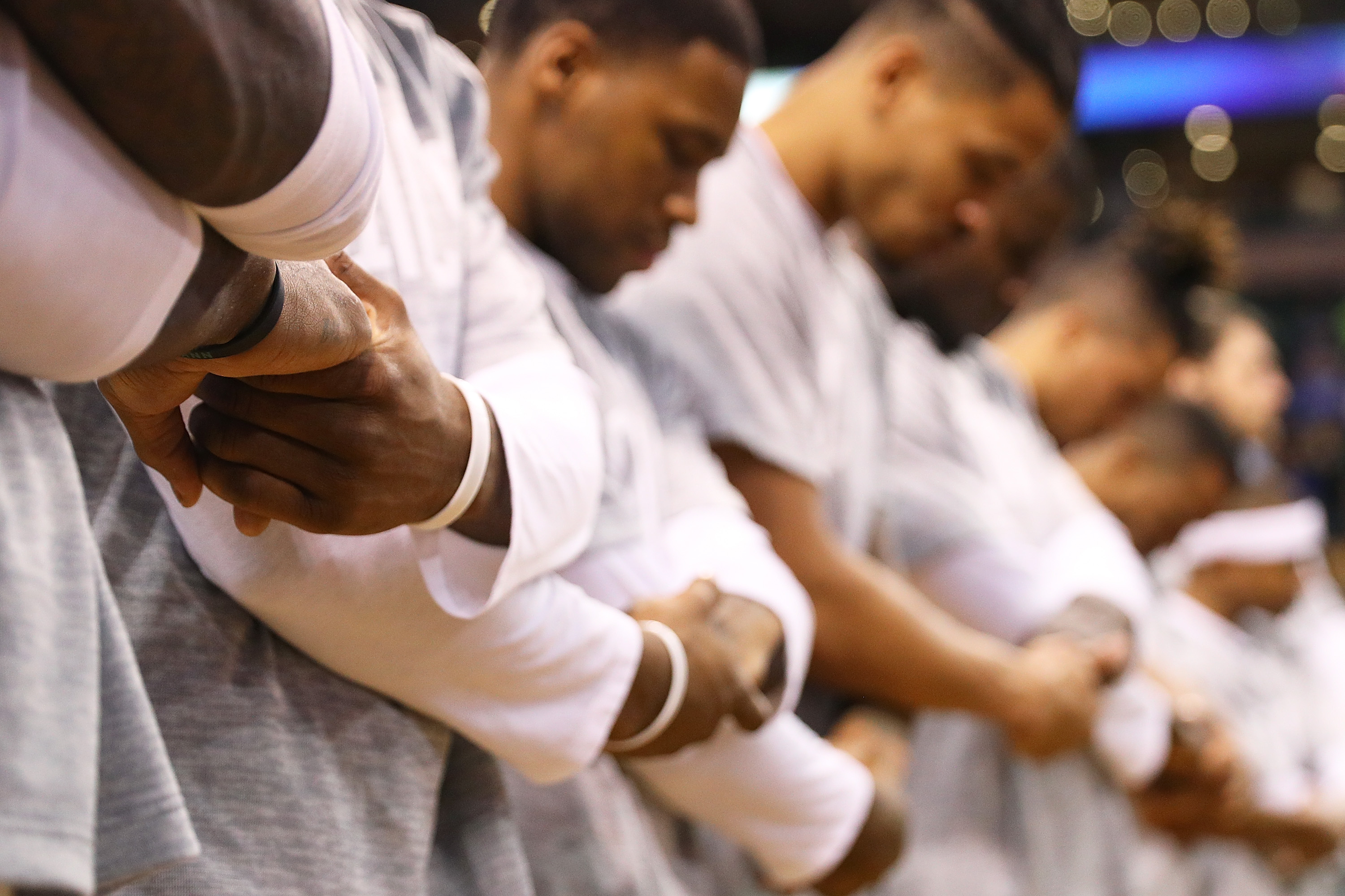 Members of the Boston Celtics link arms during the singing of the national anthem before their game against the New York Knicks at TD Garden on October 17, 2016 in Boston, Massachusetts.