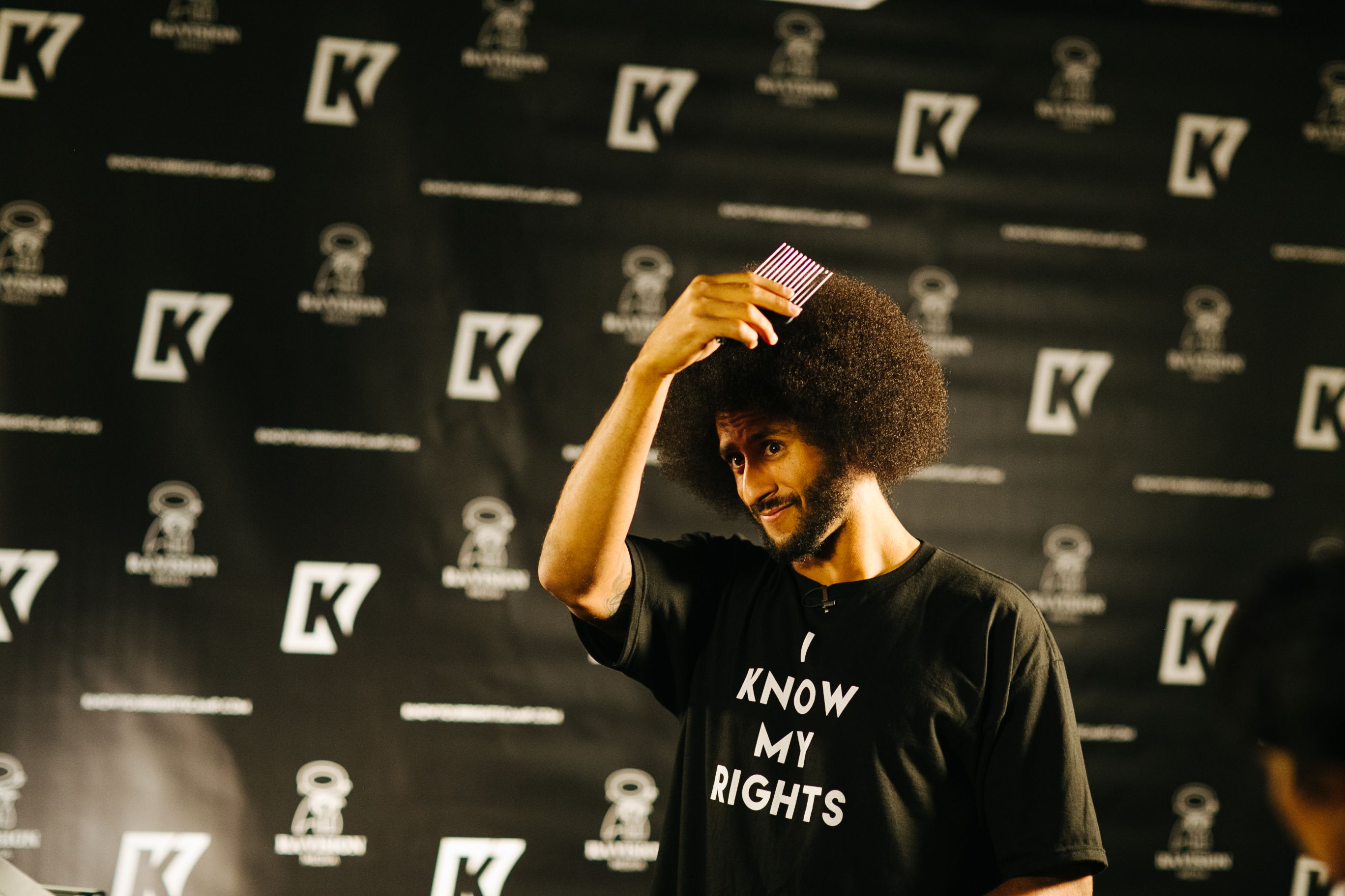 San Francisco 49ers quarterback Colin Kaepernick picks out his afro before doing an interview