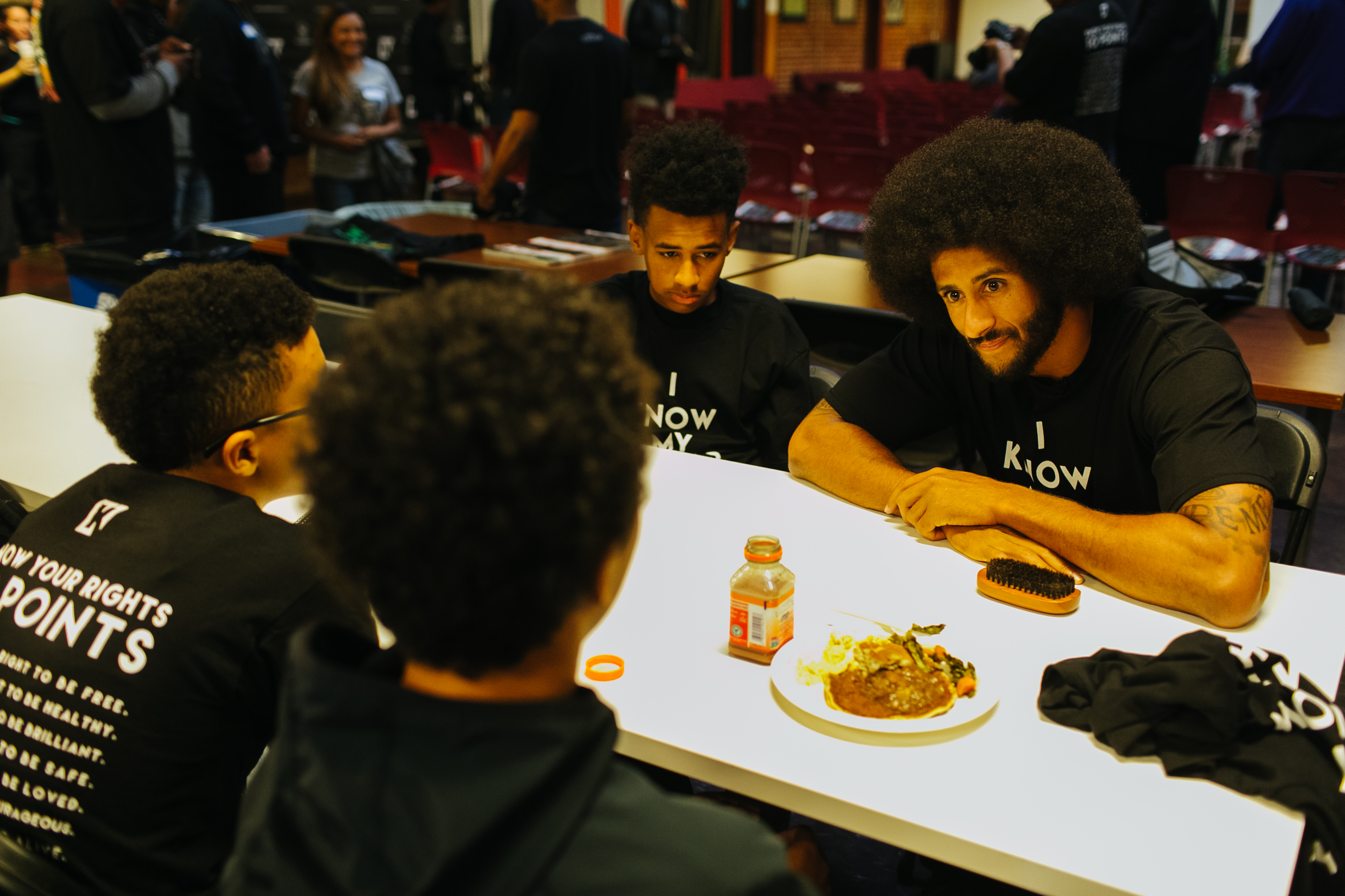 San Francisco 49ers Quarterback Colin Kaepernick talks with children over lunch at the HUB Oakland on September 29, 2016.